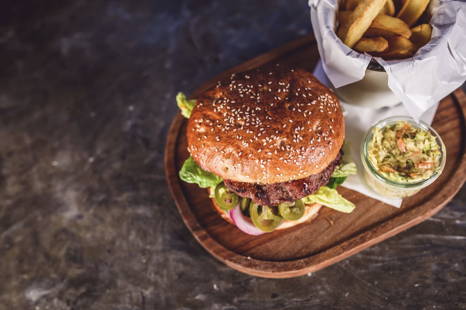 A veggie burger on a wooden plate with fries