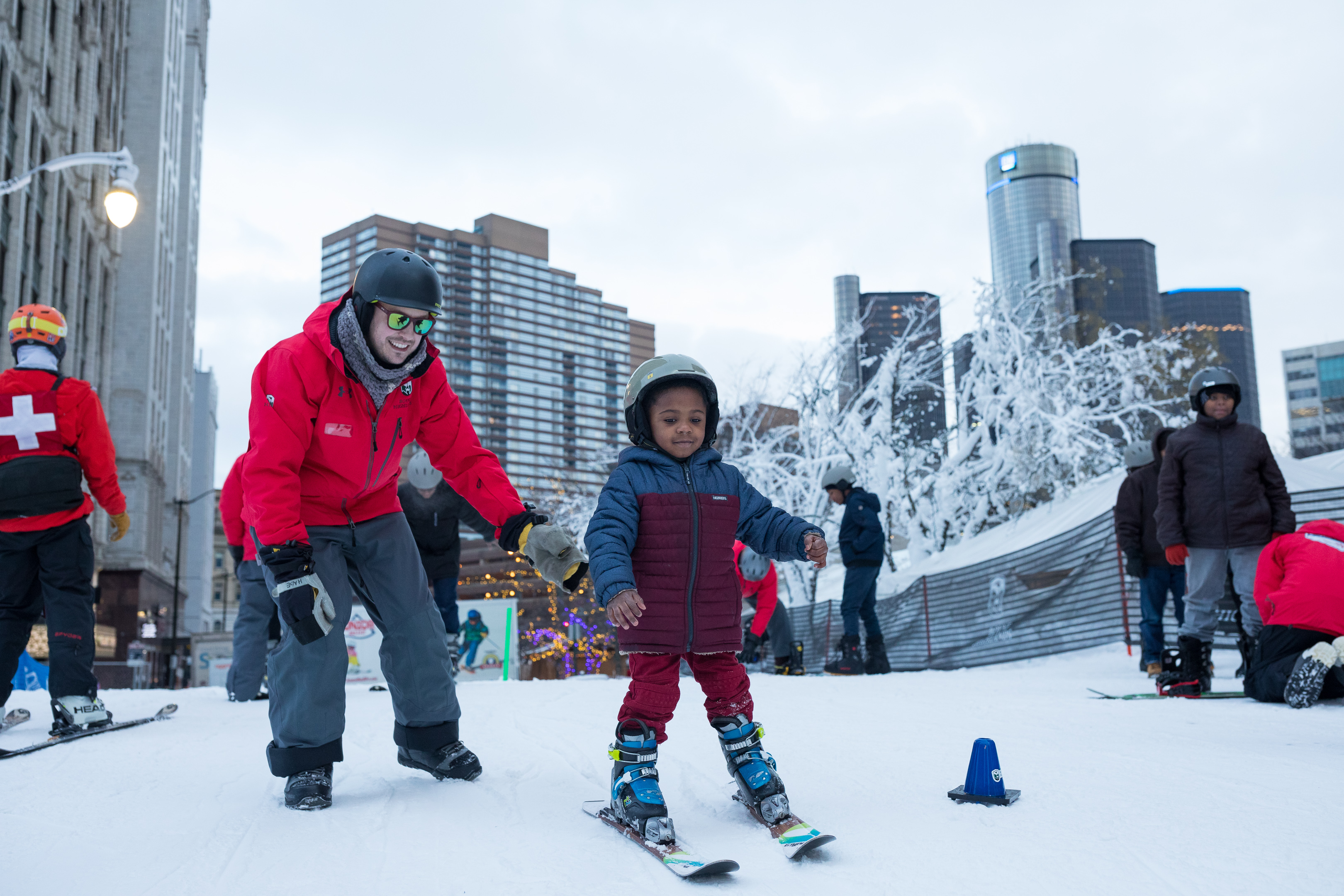 A child gently skis while an adult stands behind him. Both are smiling.