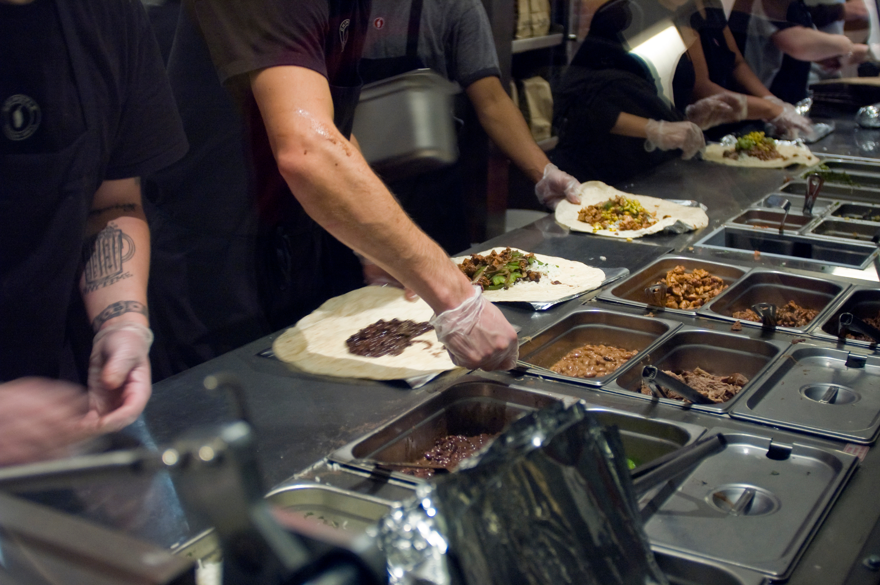 Chipotle workers scooping food onto tortillas at the counter.
