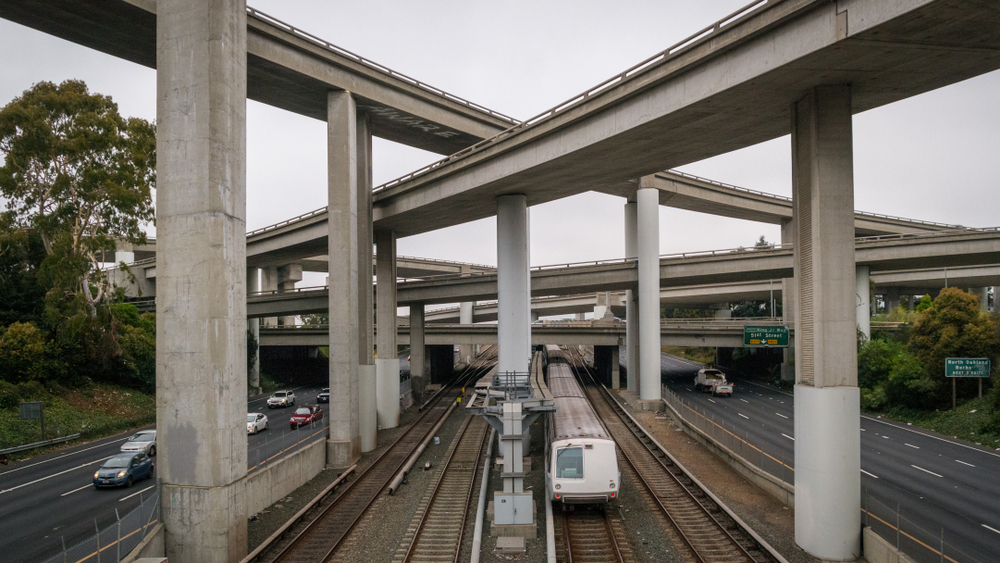 A light-rail train passing underneath criss-crossed freeway overpasses.