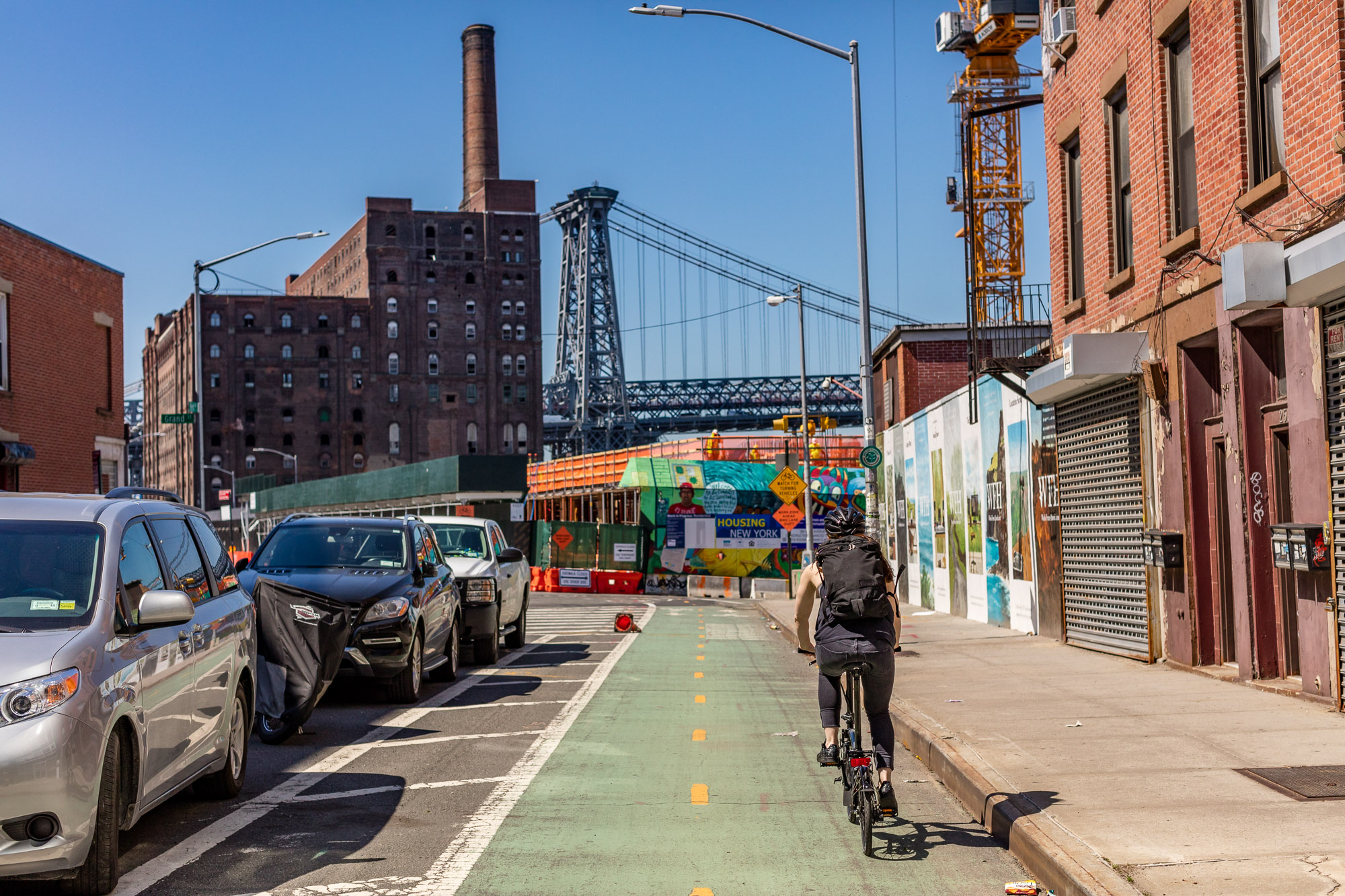A bike lane heading south along Kent Avenue, with the Williamsburg Bridge and Domino Sugar Refinery in the background.