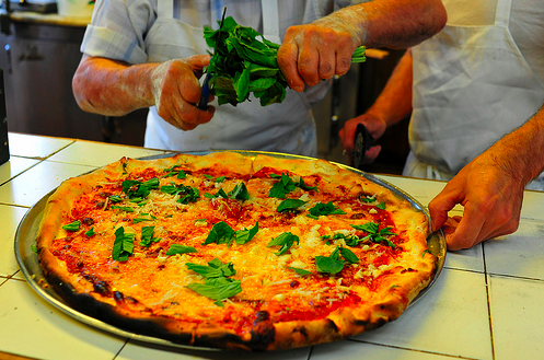 A pizza with basil on top sits on a counter, as a man's hands tears more herbs.