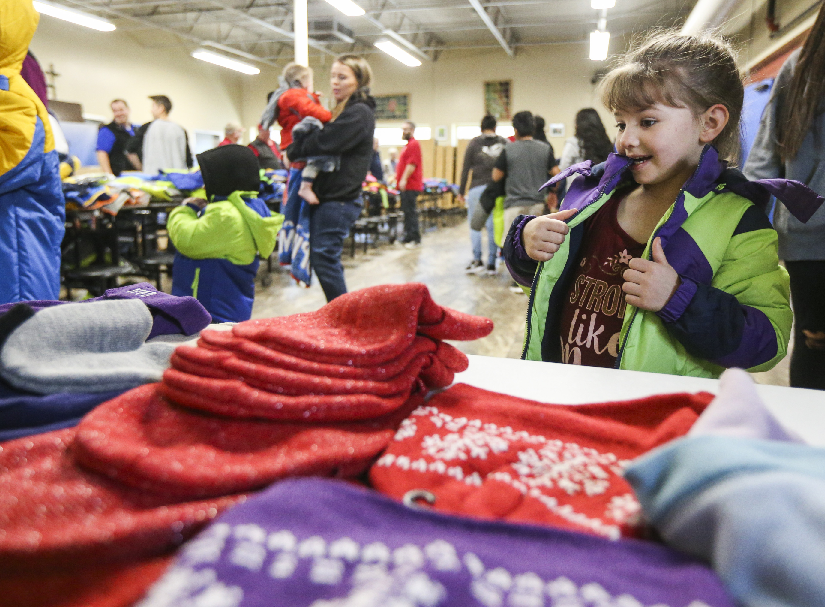 Amanda Carter, 6, eyes the piles of hats while gnawing on her new jacket during the Knights of Columbus Coats for Kids event at the St. Vincent De Paul Center in Salt Lake City on Saturday, Nov. 23, 2019. The event, which has been happening for 12 years, handed out more than 550 jackets to kids in need on Saturday.