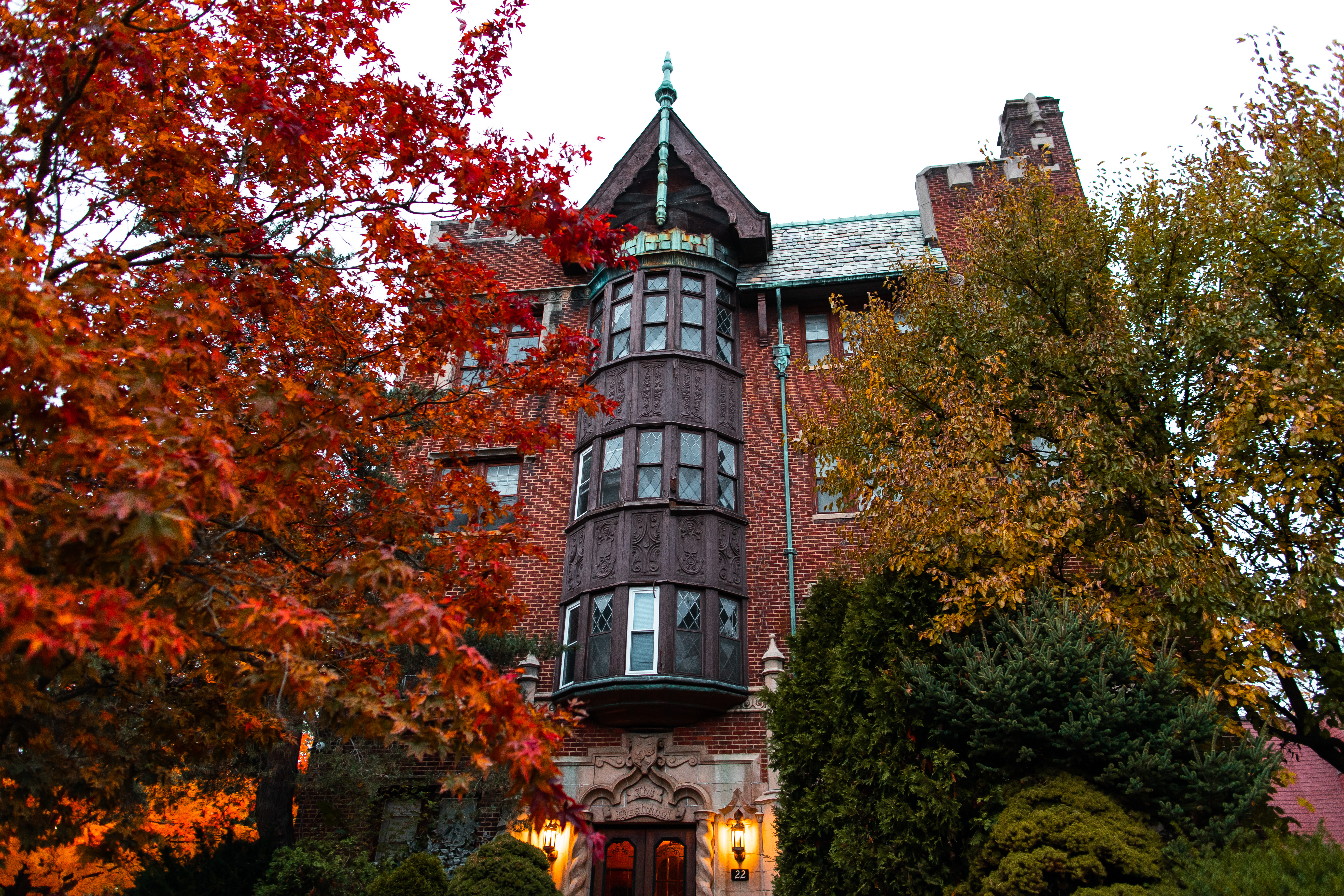 An historic apartment building surrounded by a colorful array of trees.