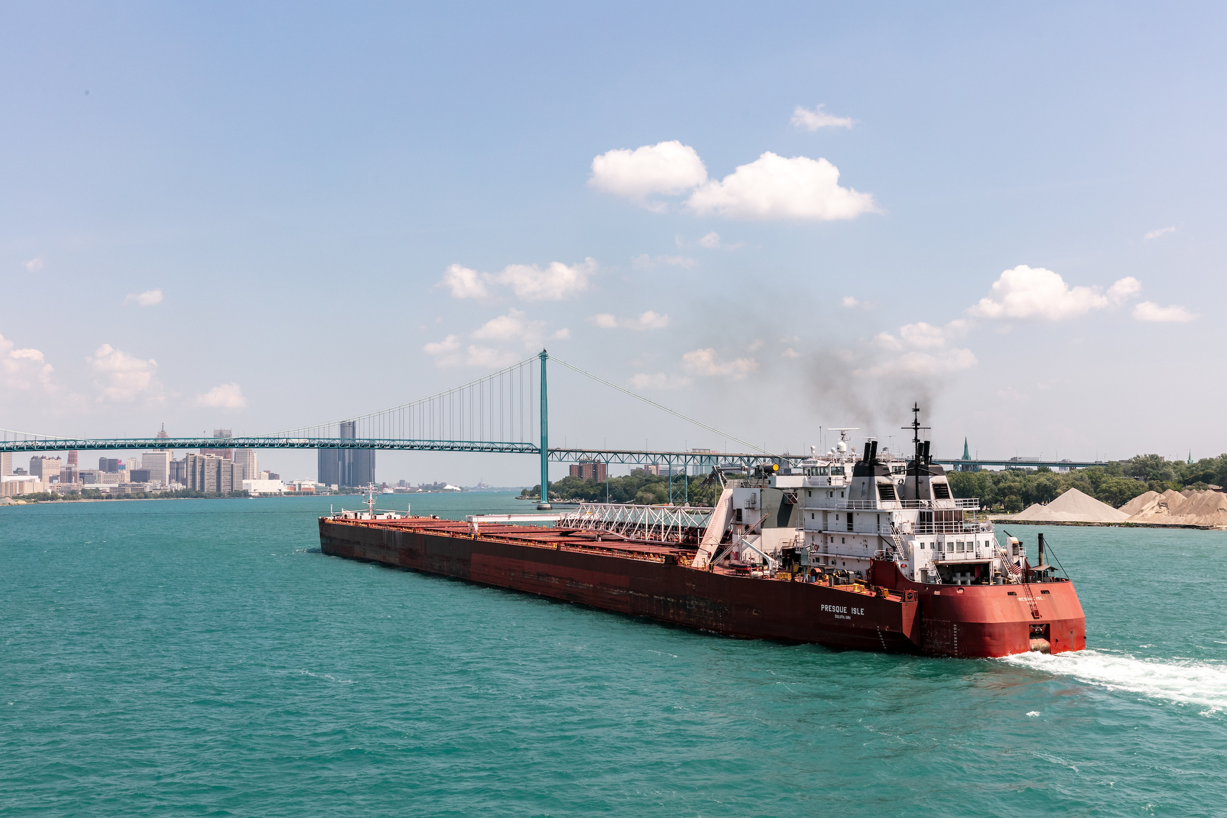 A long red and black ship in the middle of a wide river. A blue bridge can be seen in the distance.