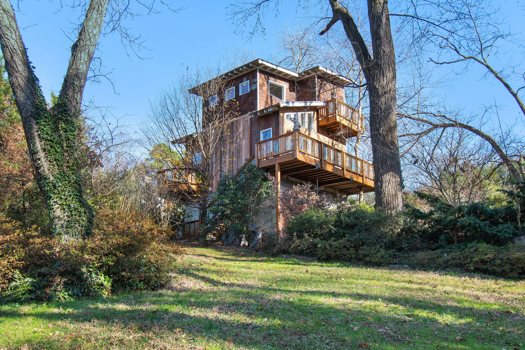 Two-story home built on stilts with trees and grass in the foreground.