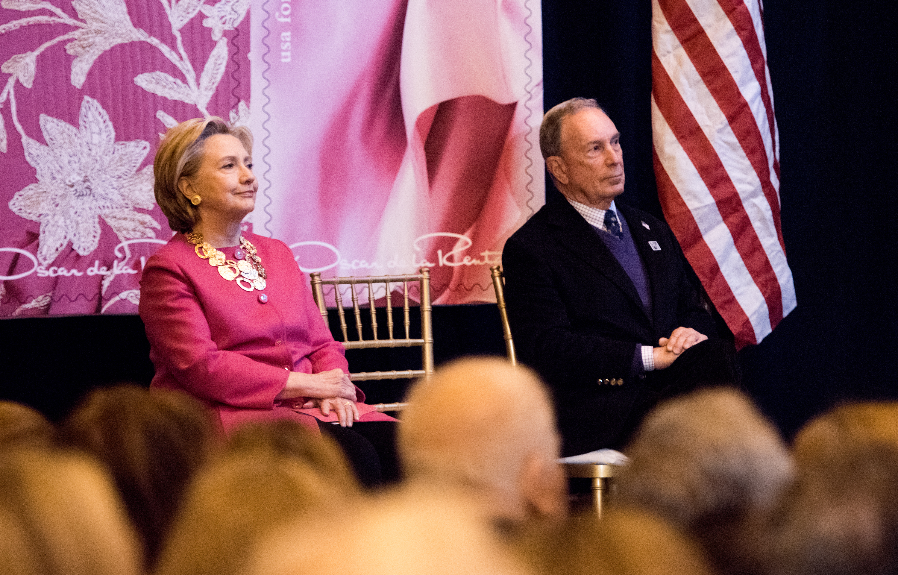 Hillary Clinton and Michael Bloomberg sit on a stage