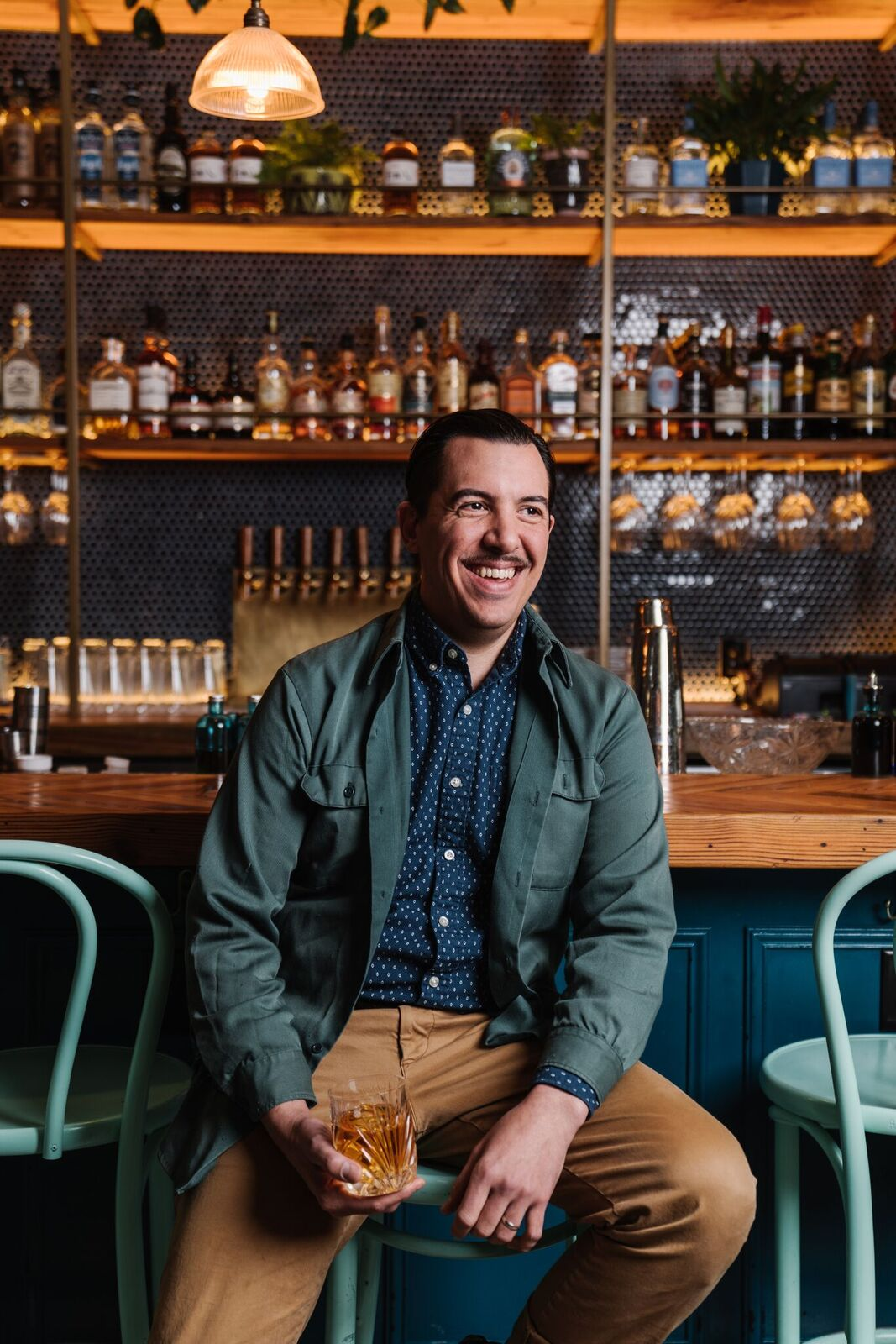 A photo of Watchman's co-owner Miles Macquarrie seated in a chair smiling in front of the bar
