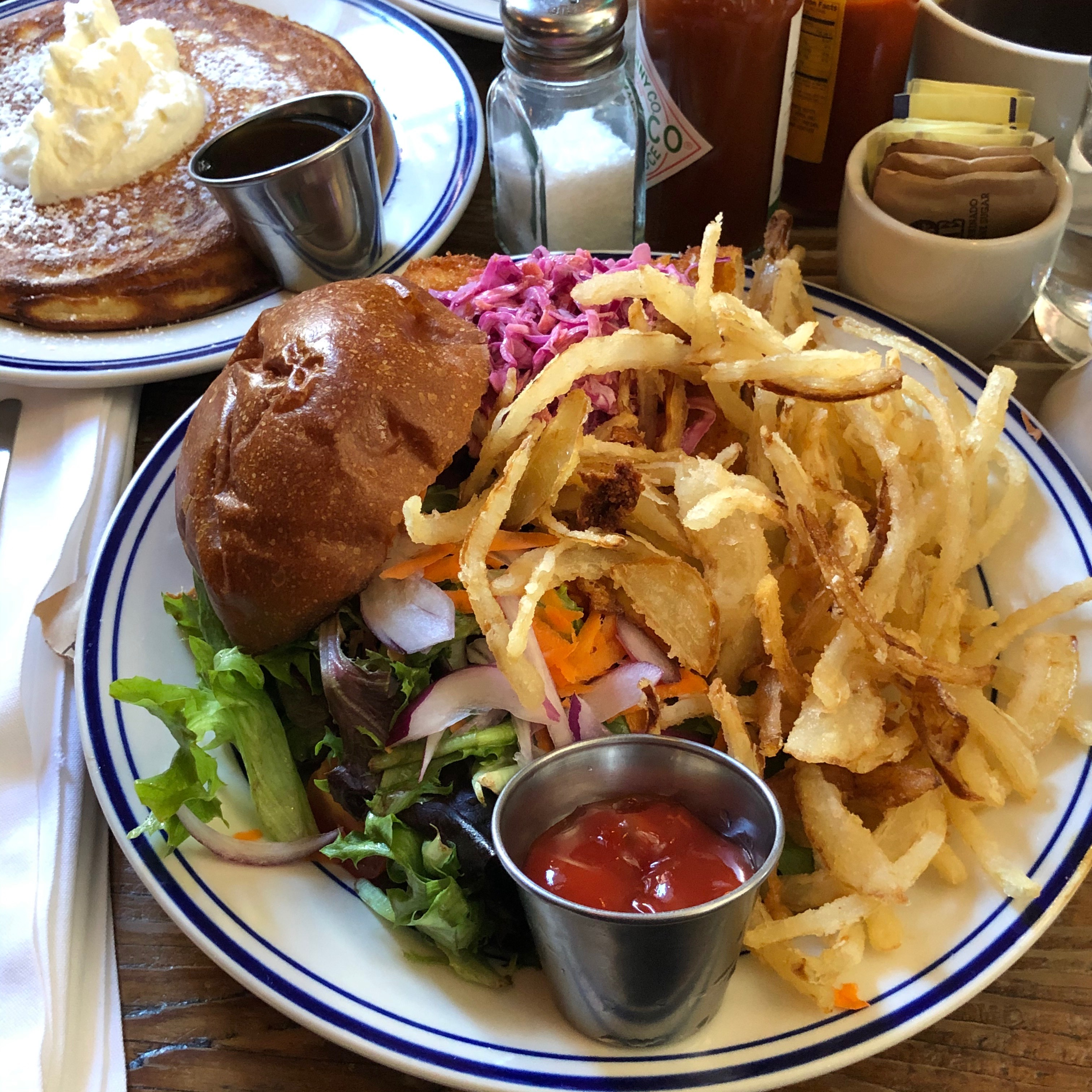 A plate of crispy, brown onion fries place next to some greens, a burger bun, and a small bowl of ketchup