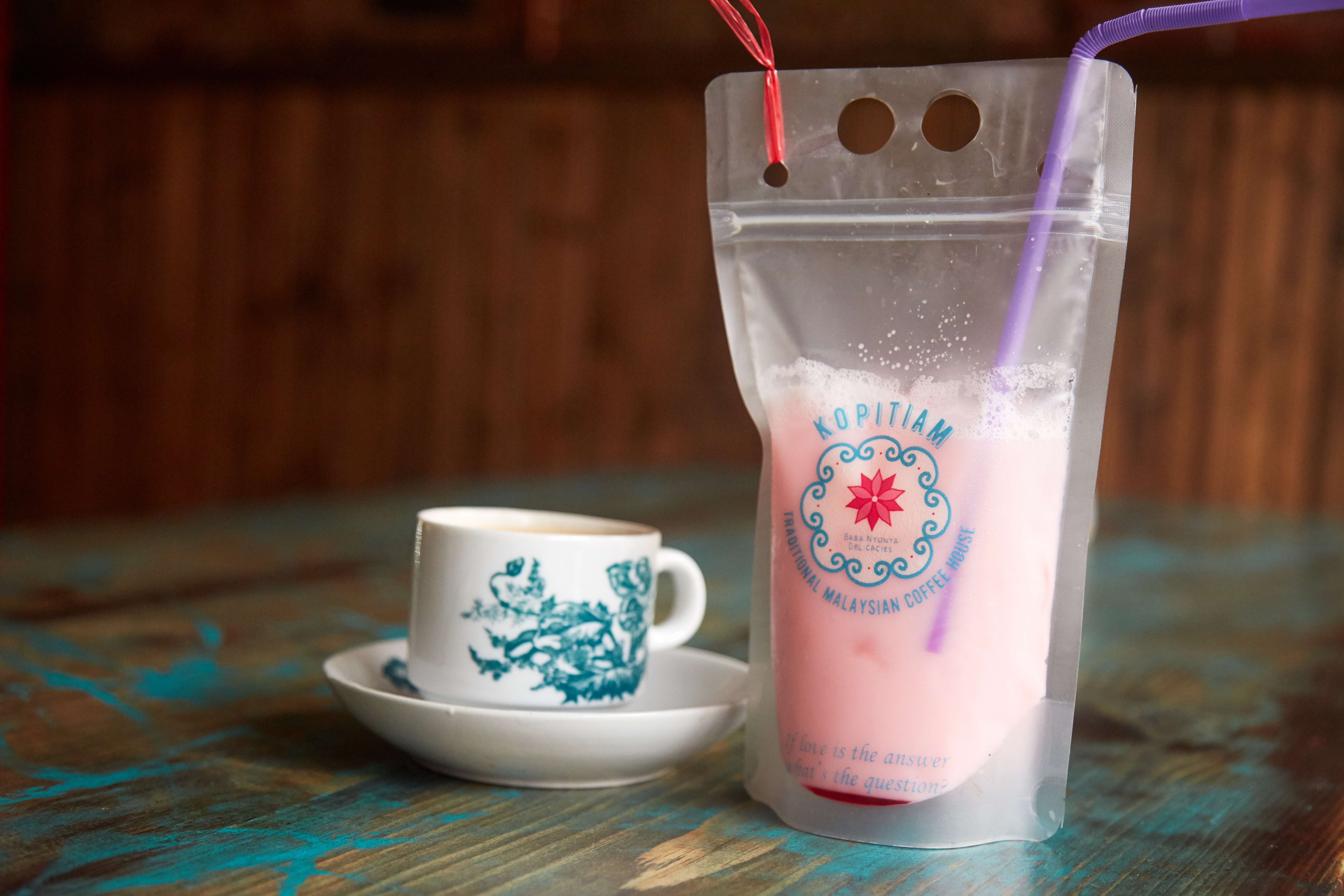 A clear plastic bag, labeled with the red and light blue logo of NYC's Kopitiam, is full of light pink liquid. It sits on a stripped wooden table next to a white teacup and saucer decorated with blue flowers.