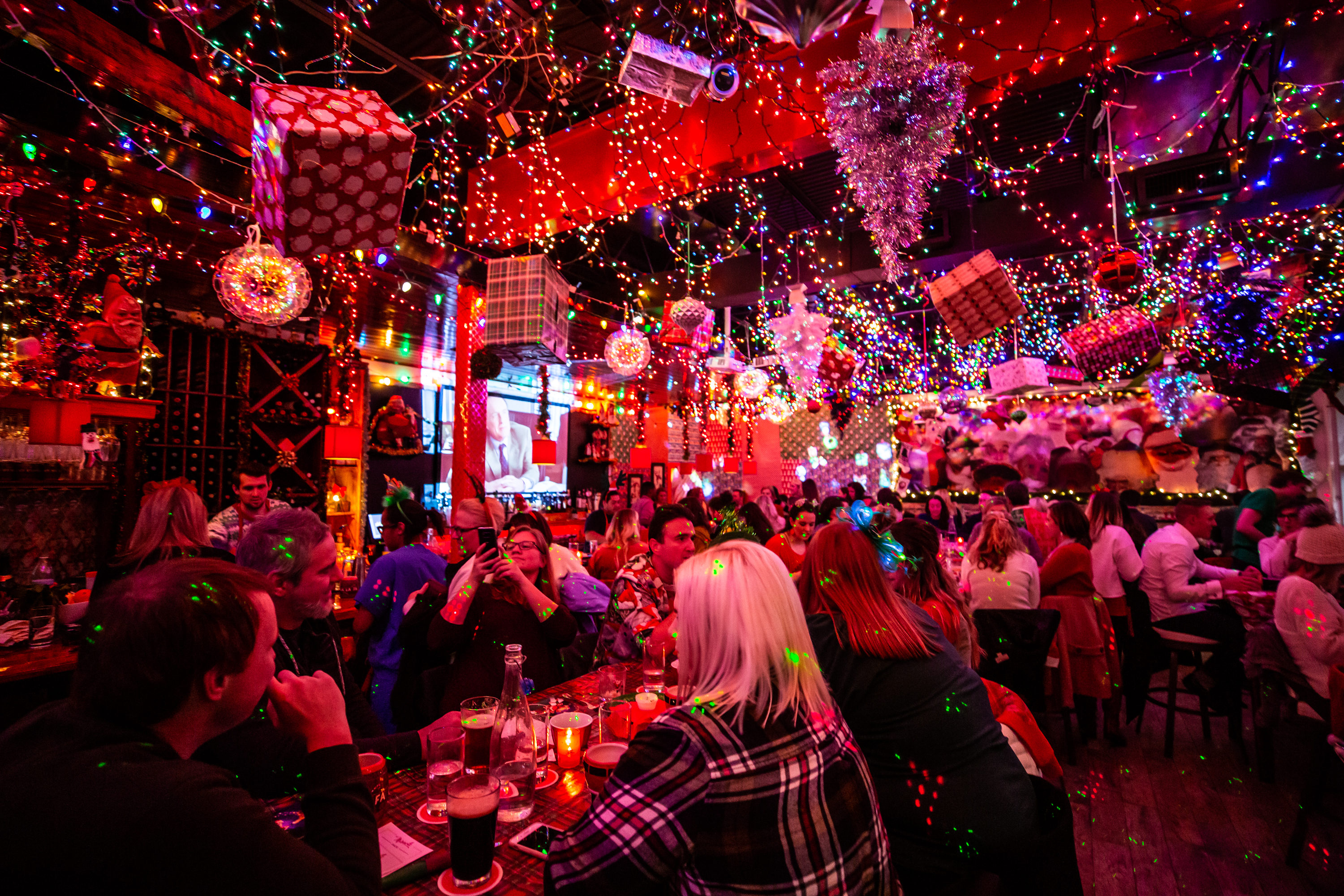 A bright light-filled bar with kitschy Christmas decorations everyone and tons of people