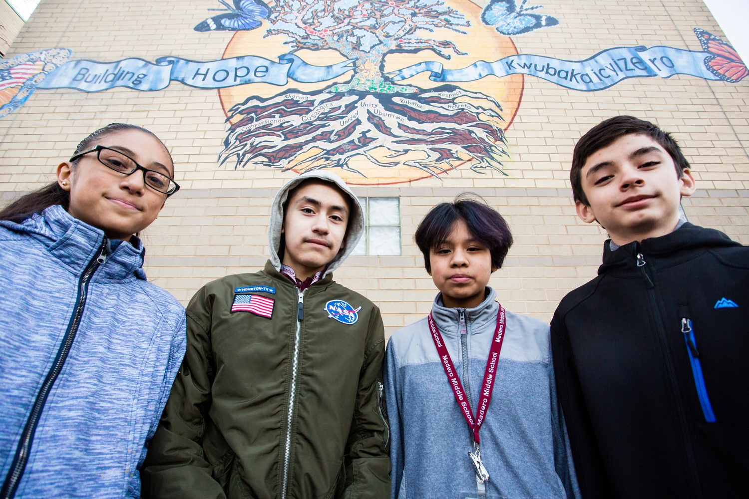 Eighth-graders Sever Menez (from left), Andrew Vargas, Cristal Palmeros and Jonatan Barahona and the new mural at Madero Middle School they helped create in collaboration with students in Rwanda,