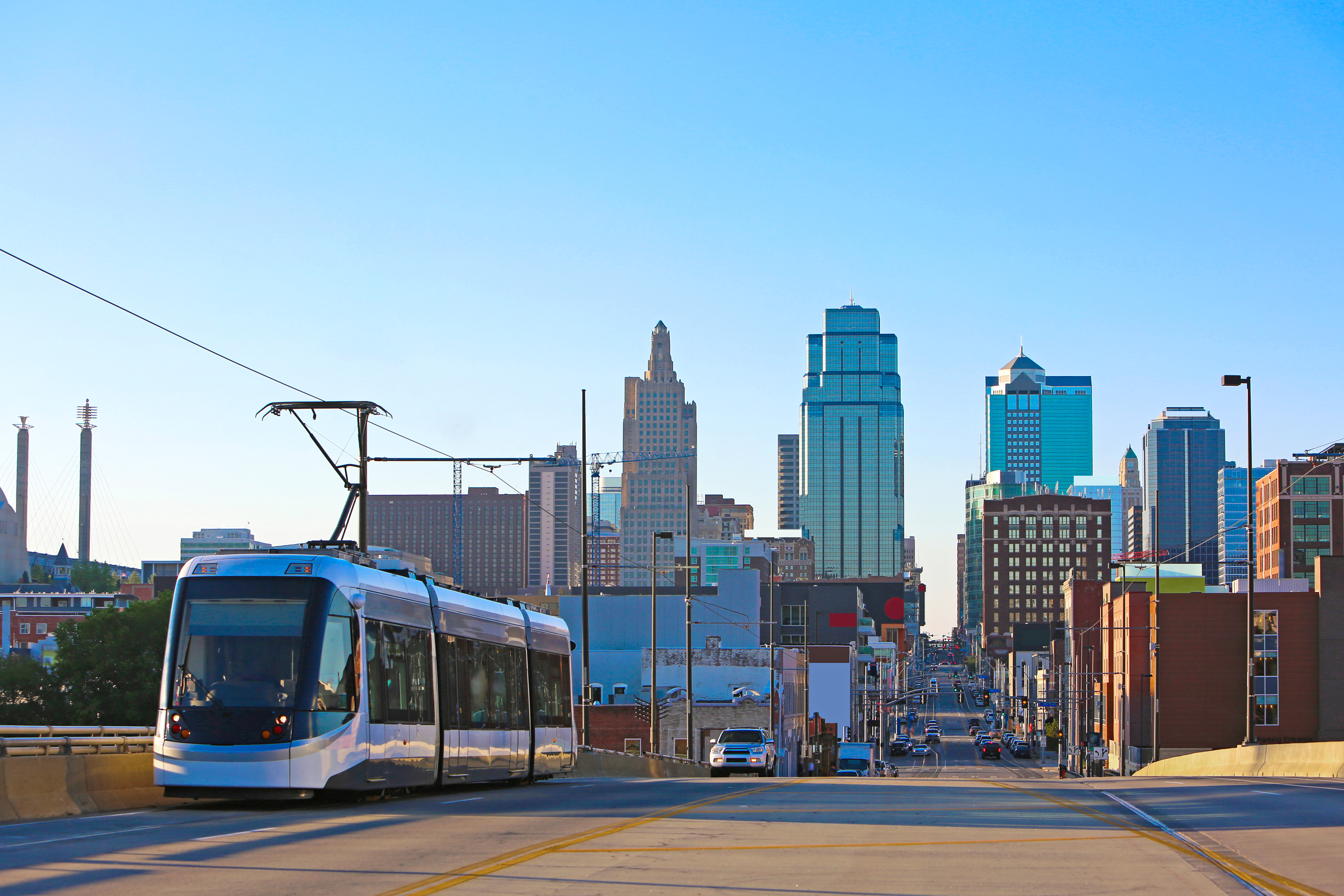 A shiny silver modern streetcar is seen surging up a wide street with a colorful city skyline seen the distance.
