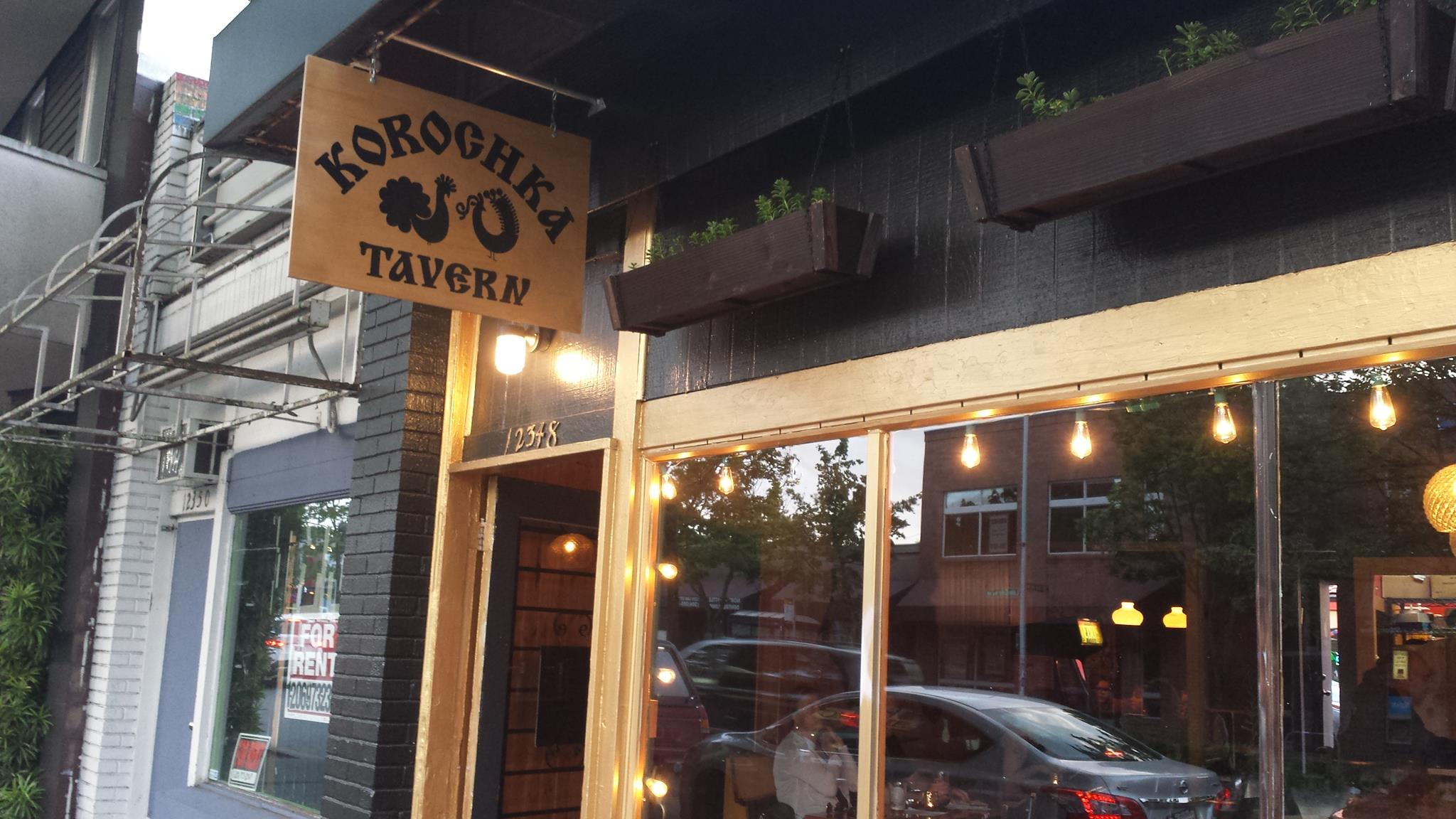The sign outside Korochka Tavern in Lake City, surrounded by lights and wood trimming.