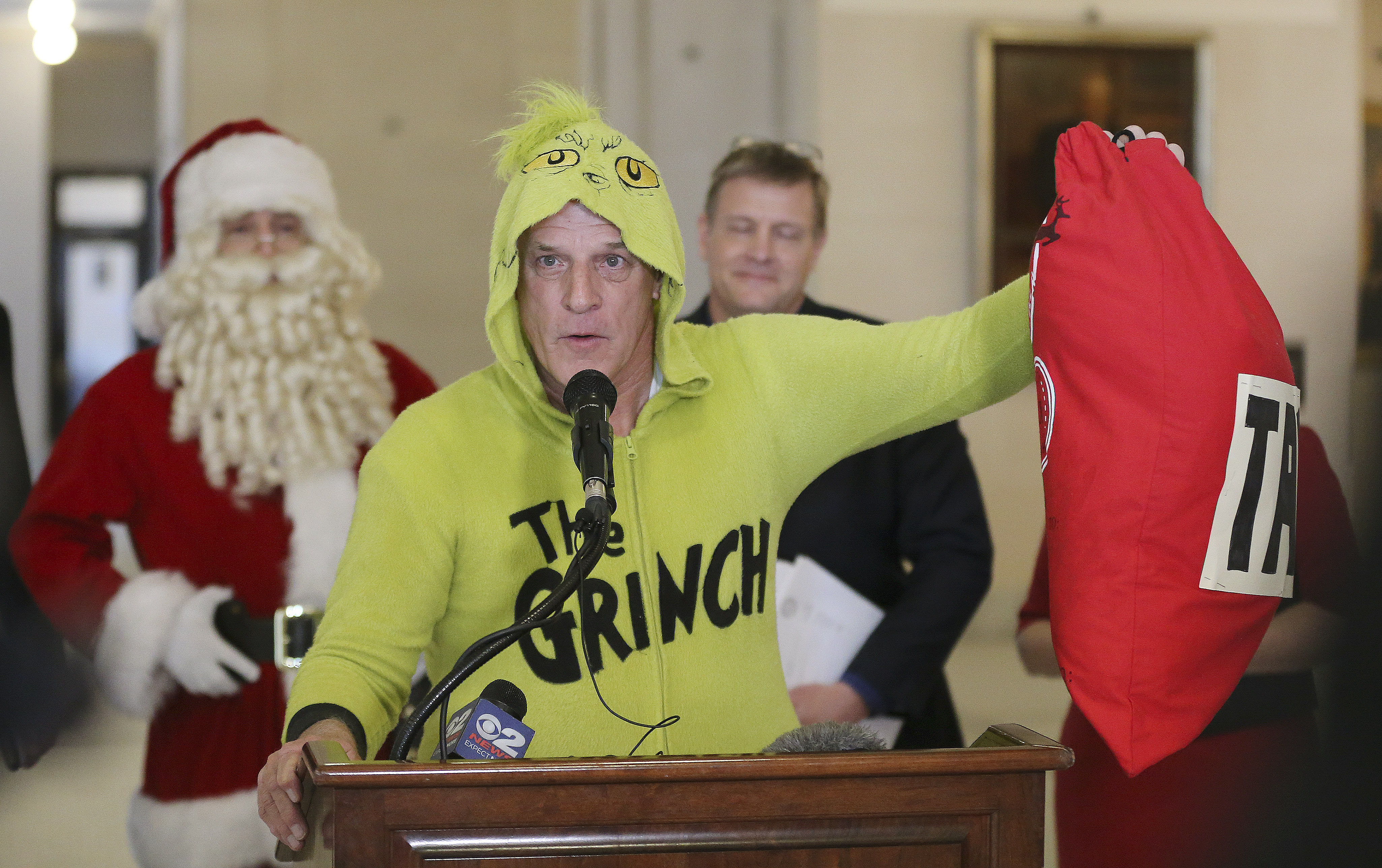 Greg Zenger, dressed as the Grinch, speaks during a press conference about tax reform at the Capitol in Salt Lake City on Friday, Dec. 6, 2019.