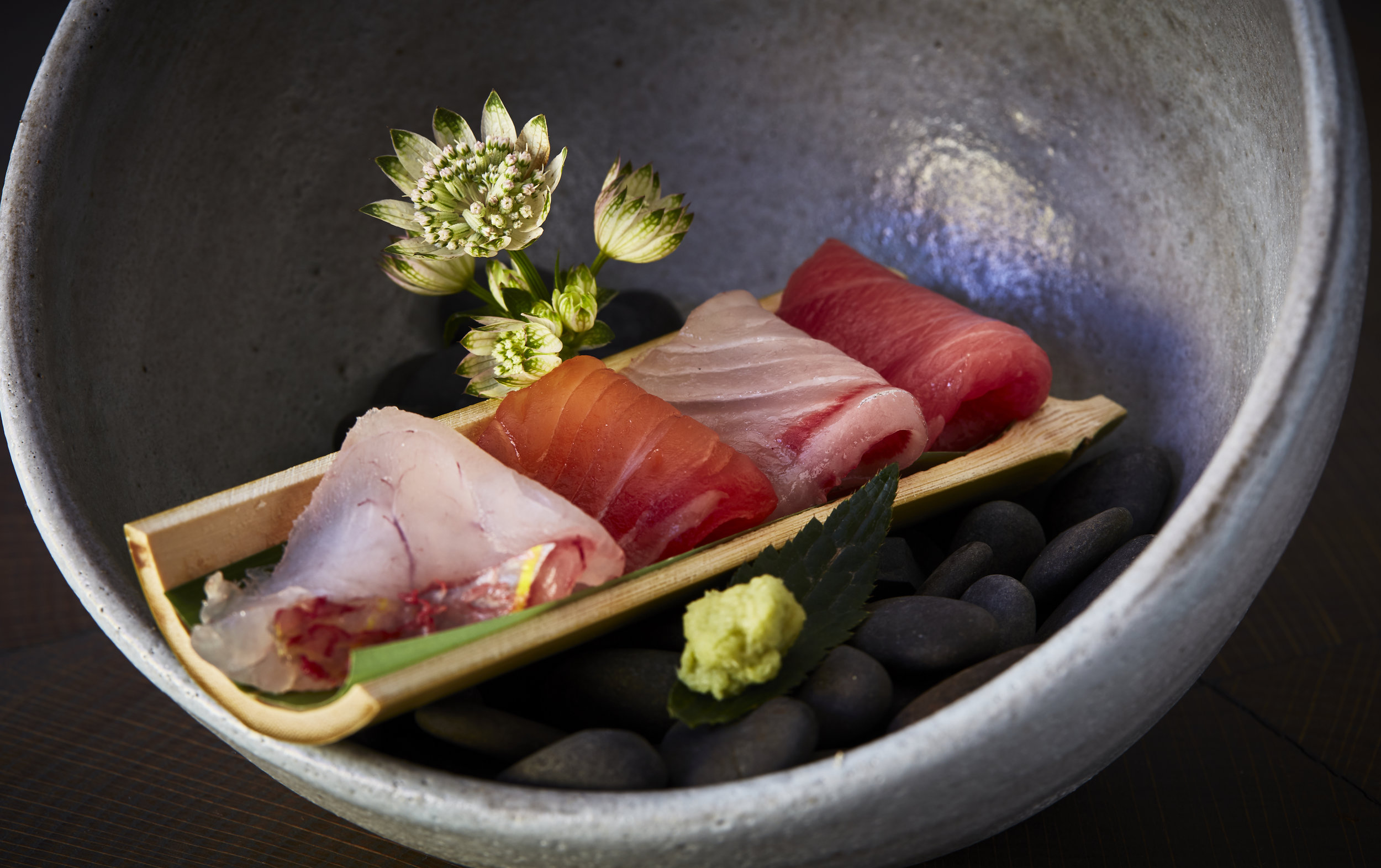 A spherical bowl contains a slice of bamboo, which olds three slices of sashimi.