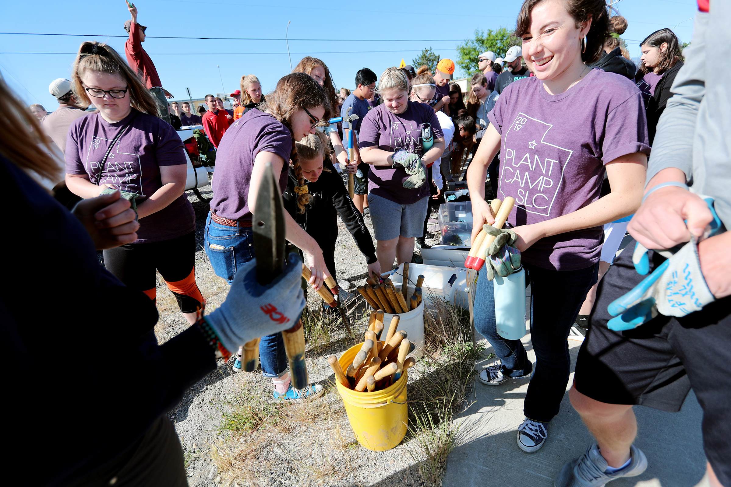 Youth from across the country pick up tools for a weed-pulling service project along the Jordan River in Salt Lake City on Friday, June 21, 2019. The service project is an extension of Gospel Grace Church's Plant Camp.
