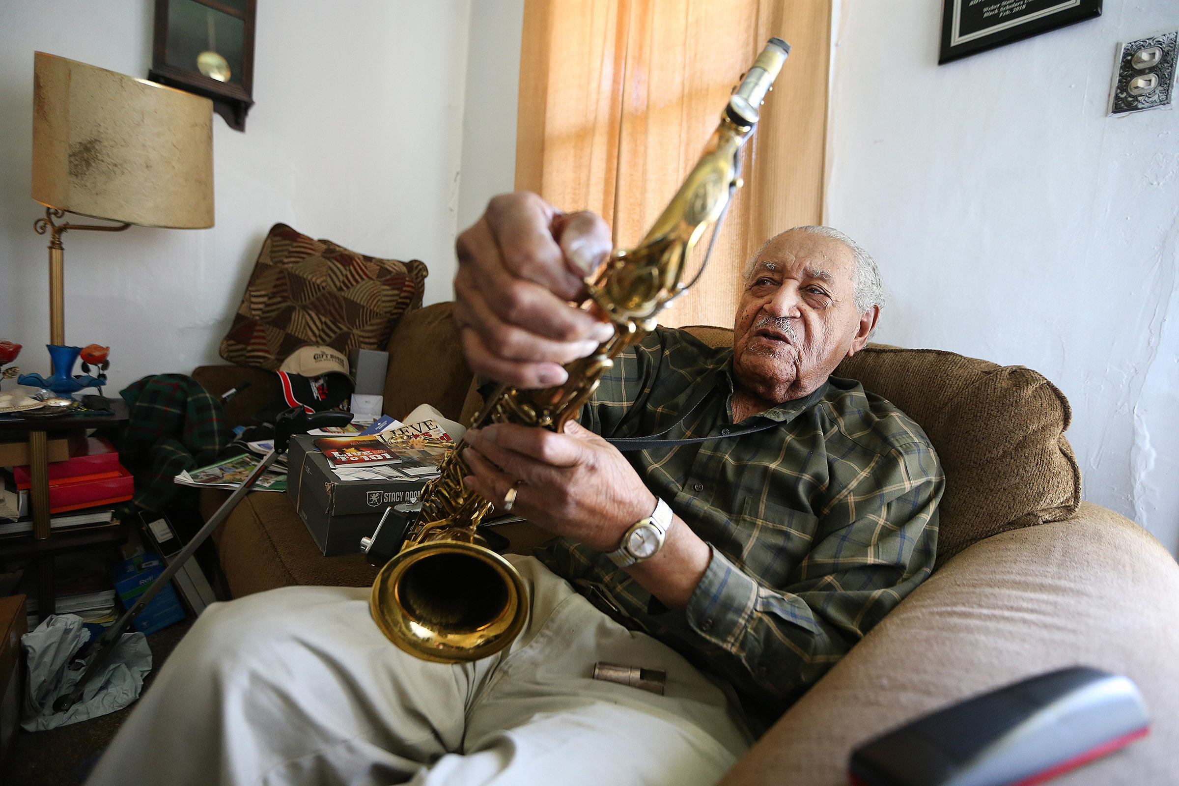 Saxophone player Joe McQueen, still going strong as he nears his 99th birthday, Joe adjusts his horn at his Ogden home on Saturday, May 26, 2018.