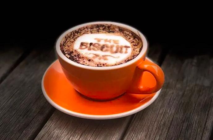 """A latte in an orange mug has """"the biscuit"""" written in the foam"""