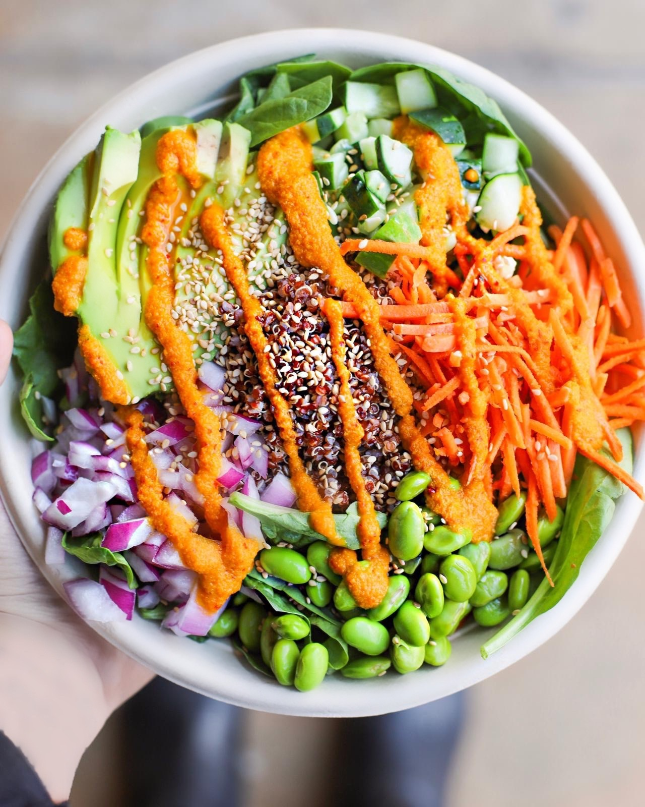 A salad bowl with carrots, avocado, edamame, chopped onion, red quinoa, and cucumbers is topped with an orange colored dressing.