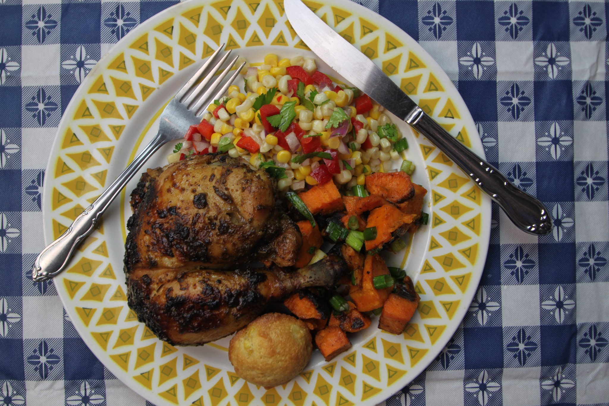 A top-down view of roasted chicken with sides of sweet potato, corn salad, and cornbread.