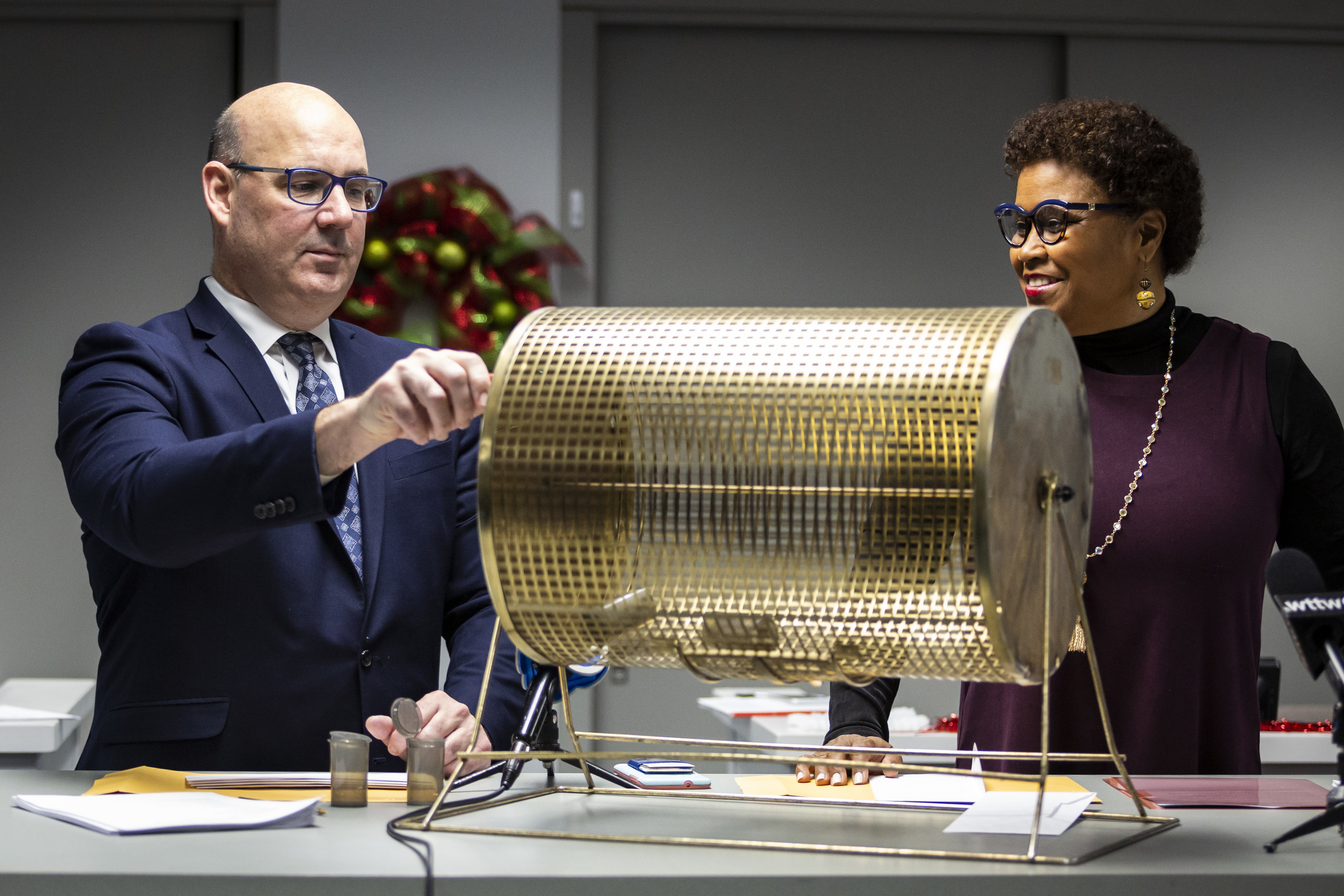 Deputy Clerk Edmund Michalowski spins a golden lottery basket for Cook County Clerk Karen Yarbrough to pull candidates' names and determine their positions on the 2020 Presidential Primary Election ballot, Monday morning, Dec. 9, 2019.