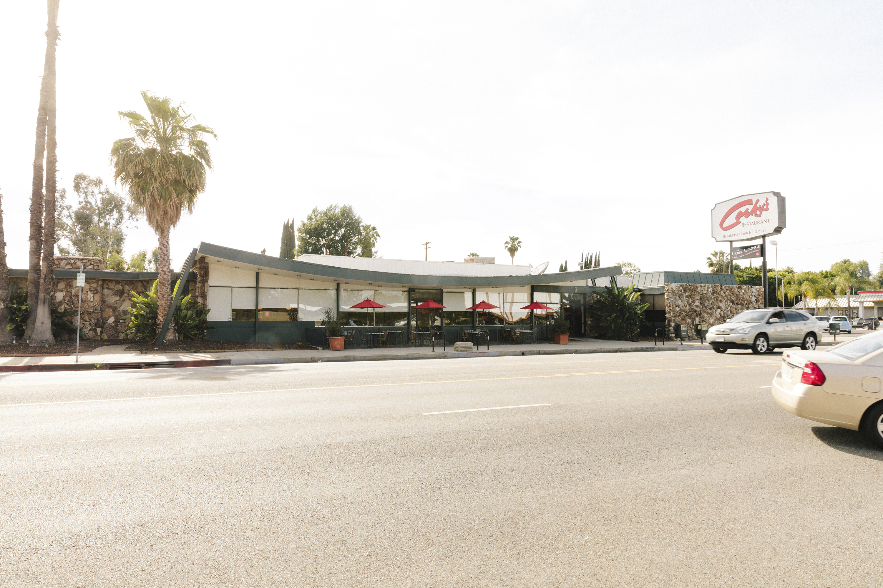 "A single-story midcentury diner with a swooping long roof and a neon sign of the restaurant's name (""Corky's)."