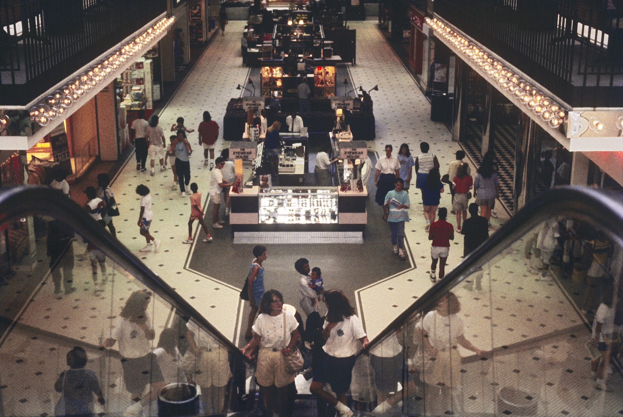 Photo from 1989 of the interior of a shopping mall looking down escalators.