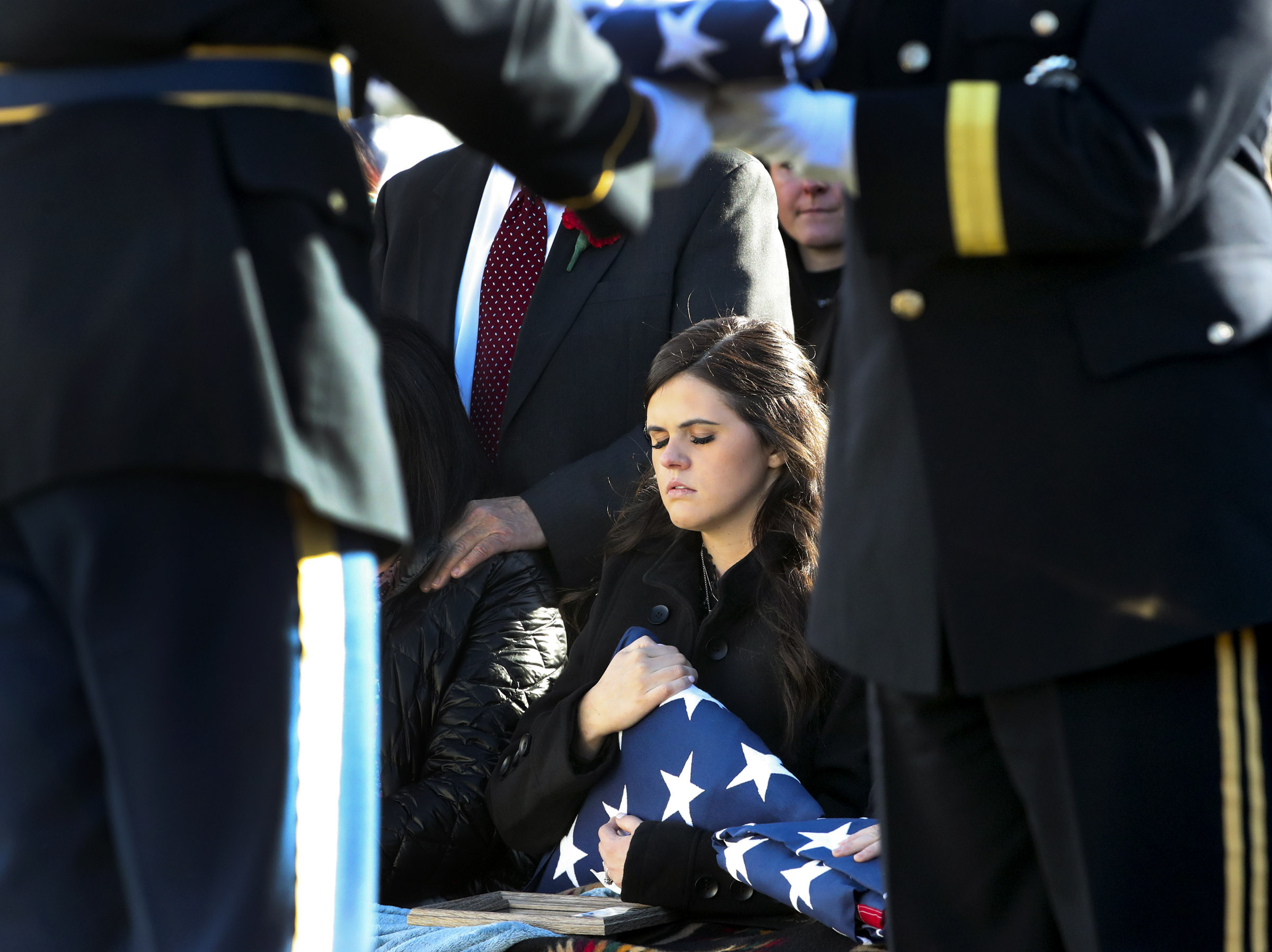 McKenzie Norman Fuchigami, wife of Chief Warrant Officer 2 Kirk T. Fuchigami Jr., holds the American flag that was draped over her husband's casket during graveside services at the Brigham City Cemetery on Monday, Dec. 9, 2019. Fuchigami and his co-pilot died when their helicopter crashed as they provided security for troops on the ground in Logar Province in eastern Afghanistan.