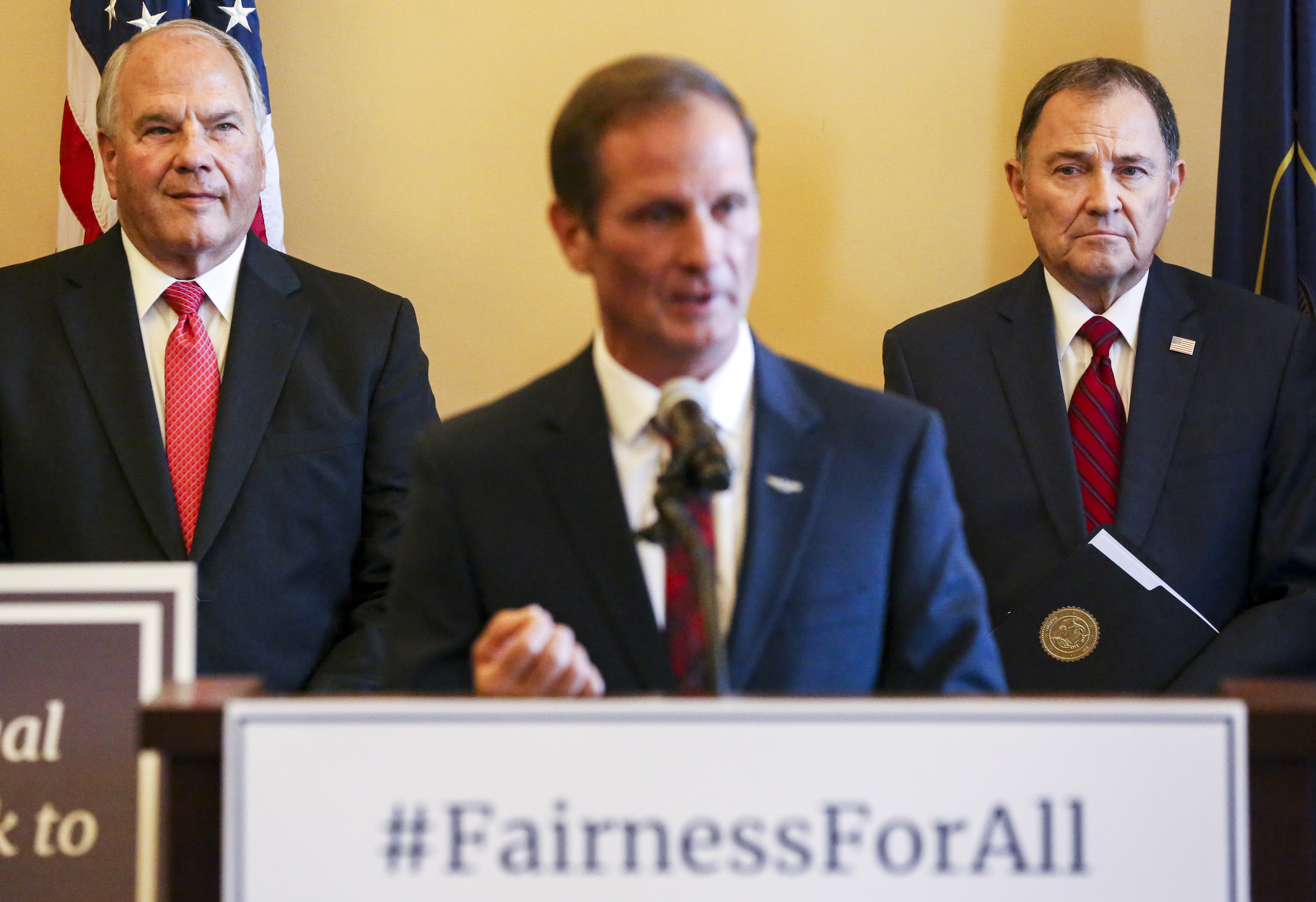 Elder Ronald A. Rasband of the Quorum of the Twelve Apostles of The Church of Jesus Christ of Latter-day Saints, left, and Utah Gov. Gary Herbert, right, listen to Utah Rep. Chris Stewart speak during a press conference to introduce the Fairness for All Act at the Utah State Capitol in Salt Lake City on Monday, Dec. 9, 2019.