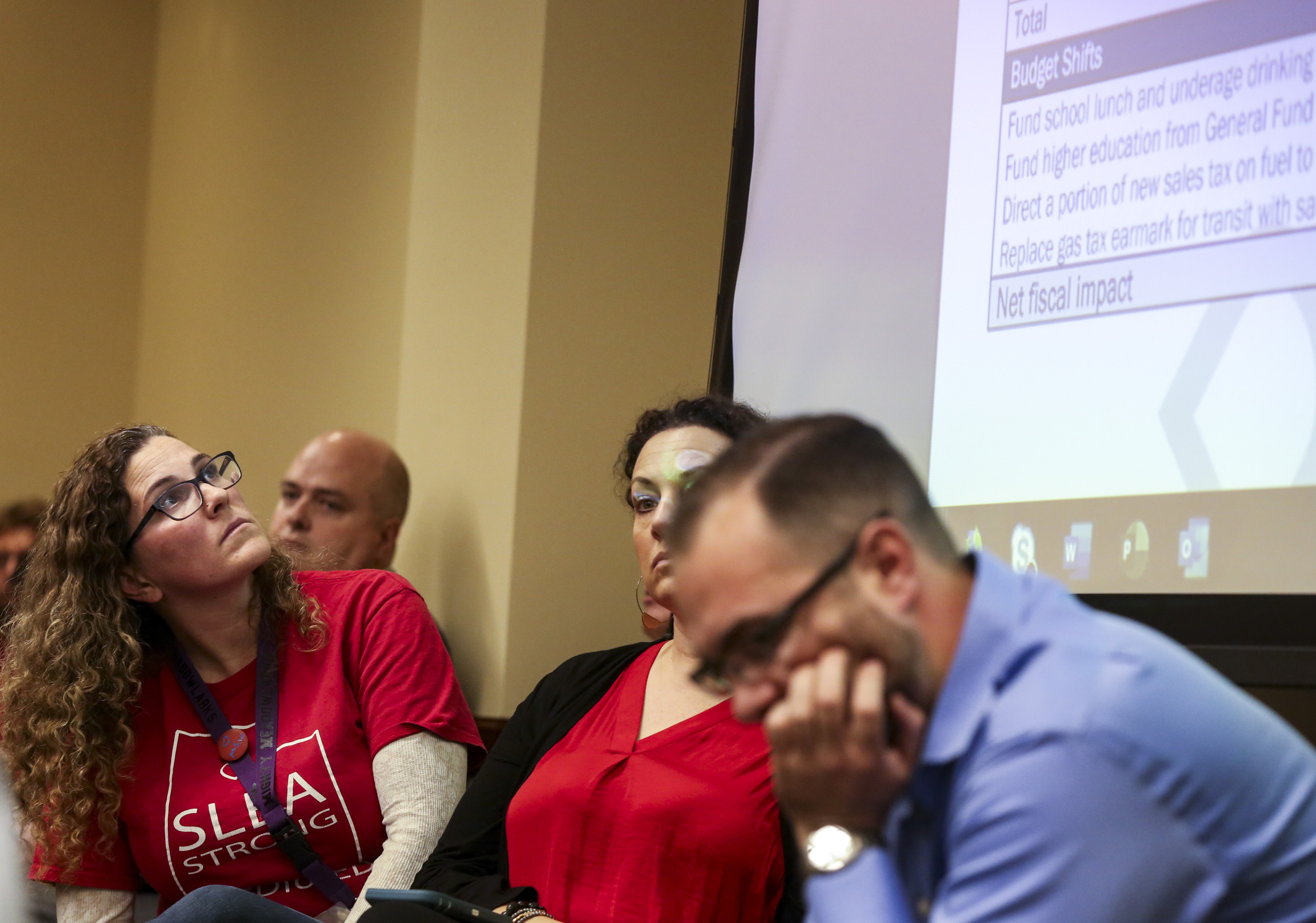 Jennifer Woznick, left, with the Salt Lake Education Association, looks at a projection screen of a state budget breakdown during a Tax Restructuring and Equalization Task Force meeting at the Capitol in Salt Lake City on Monday, Dec. 9, 2019.