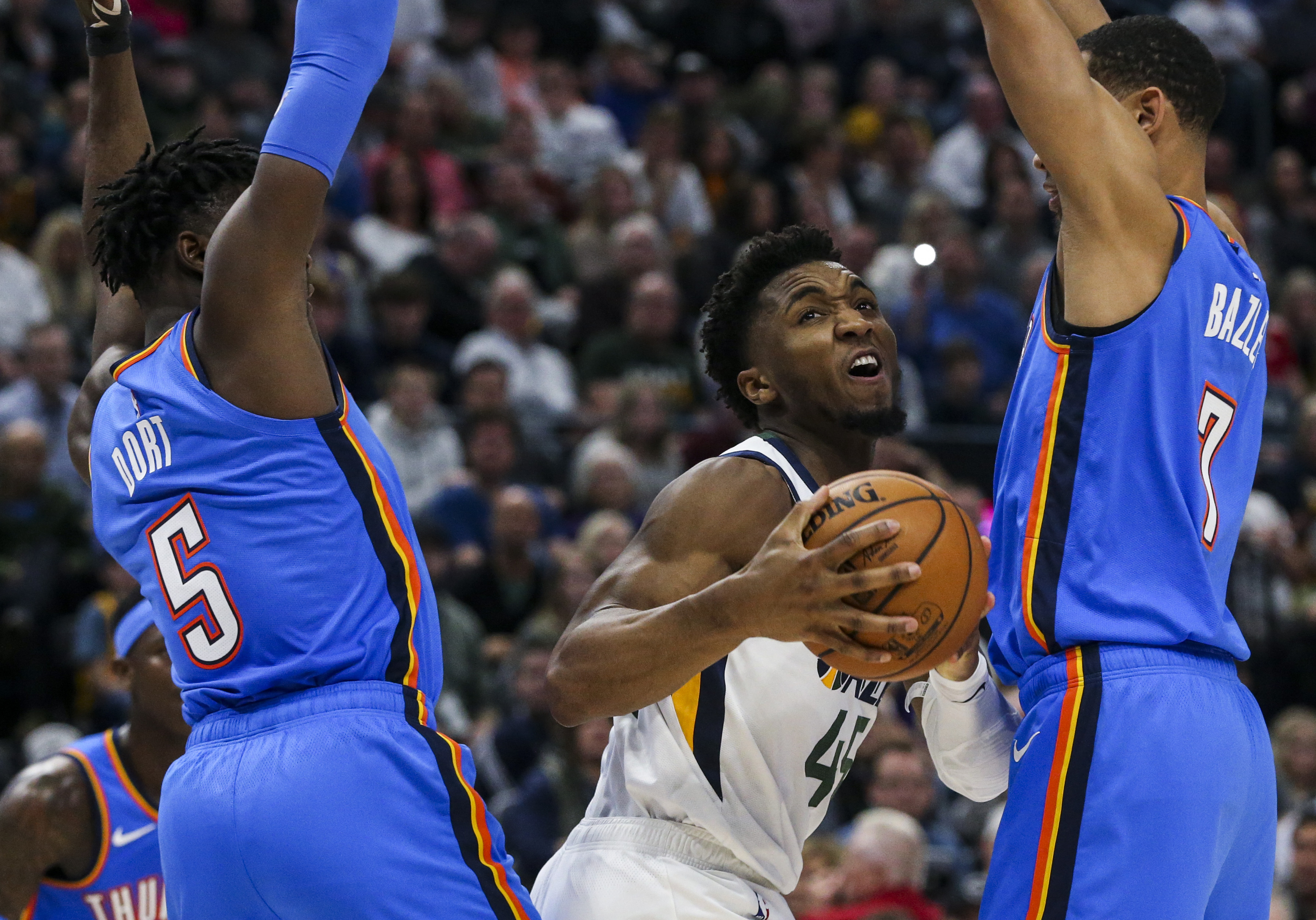 Utah Jazz guard Donovan Mitchell (45) is boxed in by Oklahoma City Thunder guard Luguentz Dort (5) and forward Darius Bazley (7) during the first half of a NBA basketball game at Vivint Smart Home Arena in Salt Lake City on Monday, Dec. 9, 2019.