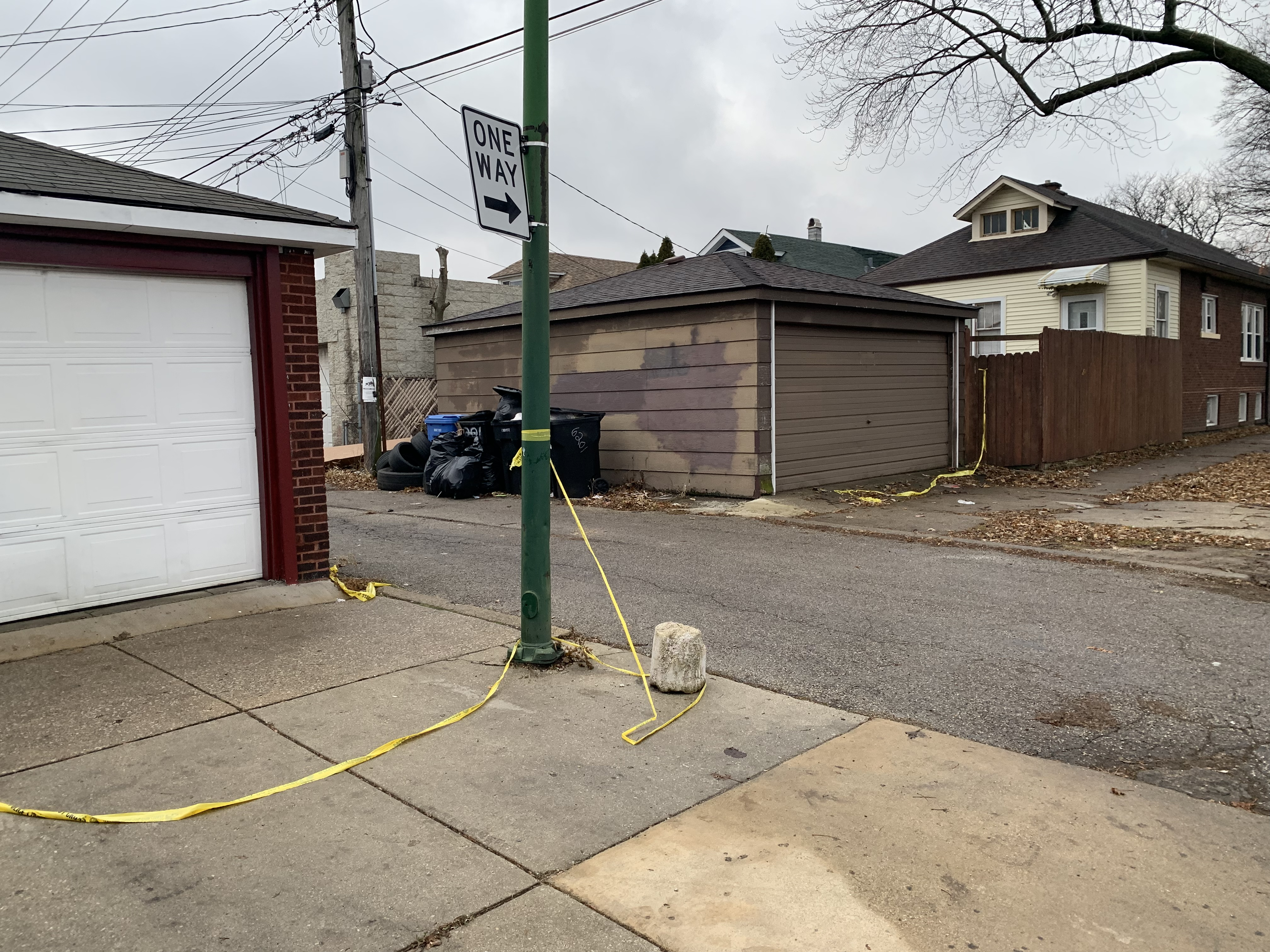 Yellow police tape remained at the north exit of an alley in the 6200 block of South Mozart Street where two men were killed during a shootout Monday morning.