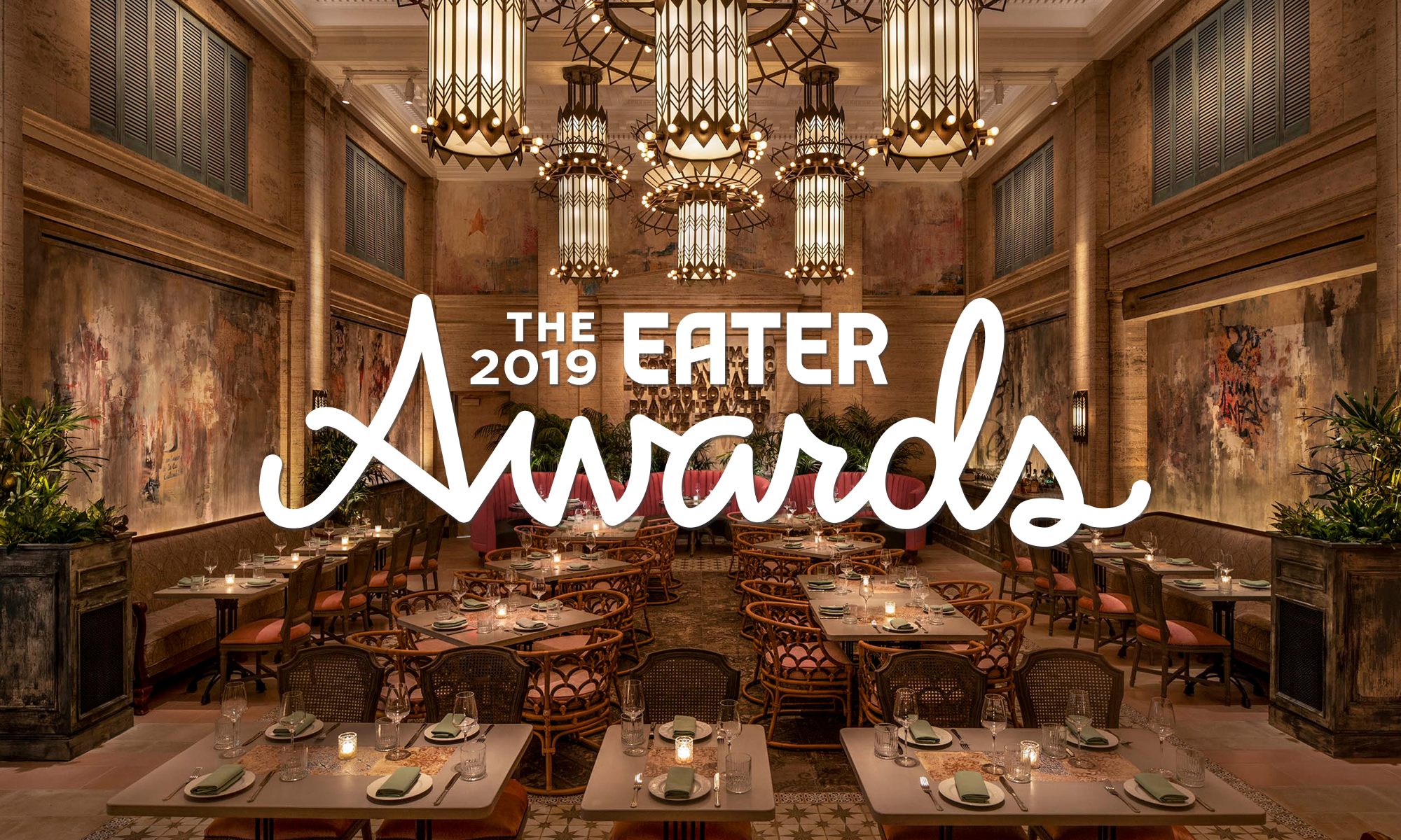 """A high-ceilinged restaurant with grand chandeliers, red plush seating, and wood accents. The words """"the 2019 Eater Awards"""" are superimposed on the image."""