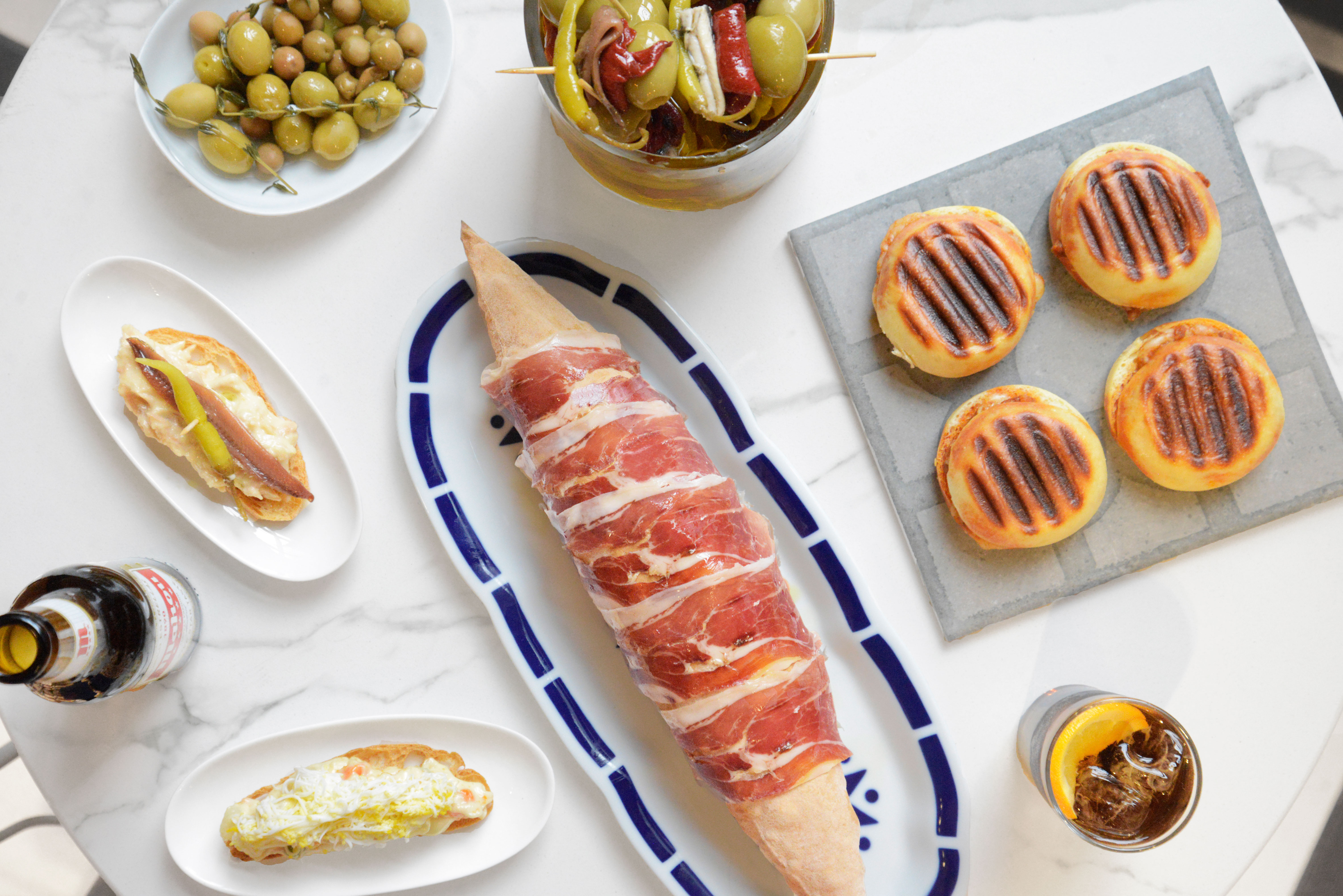 A marble table that's topped with several dishes include a baguette wrapped in prosciutto, a bowl of olives, and a cocktail.