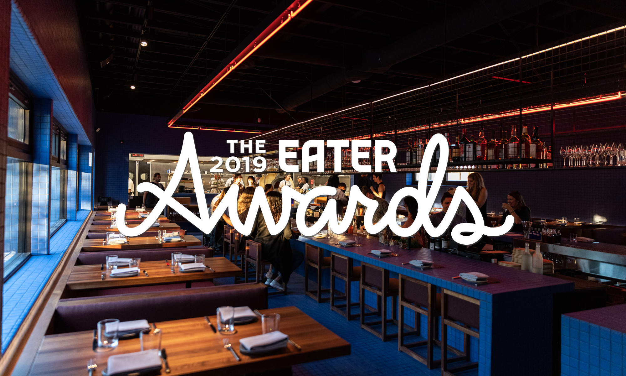 "A blue tiled room with wood tables at Magnet with ""The 2019 Eater Awards"" written in white across the front of the image."