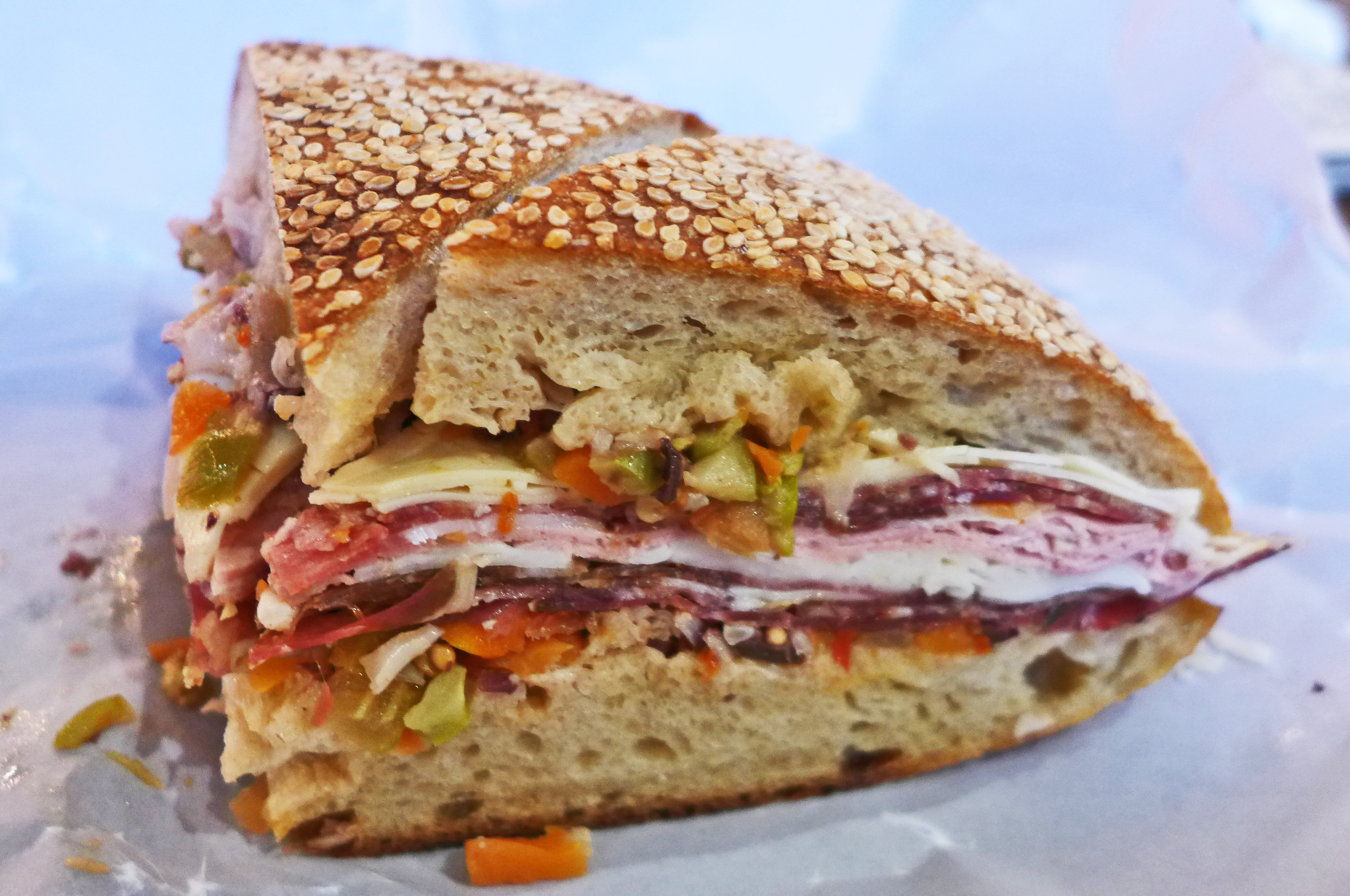 A quarter wedge of round sesame bread piled with cold cuts.