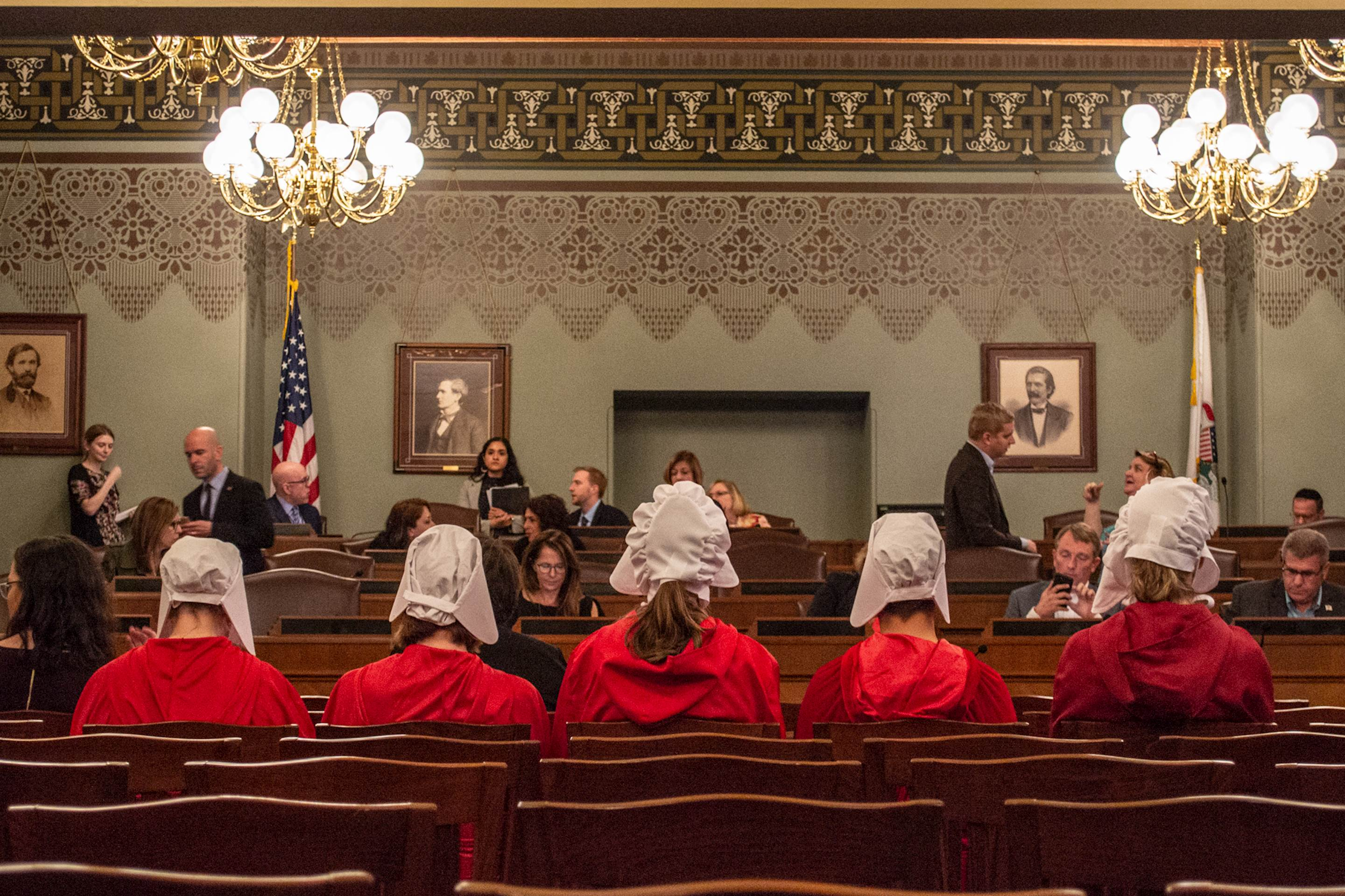 "Women dressed as Handmaids, characters from Margaret Atwood's dystopian novel, ""The Handmaid's Tale,"" sit as a House committee prepares to debate the Reproductive Health Act on Sunday at the Capitol in Springfield."