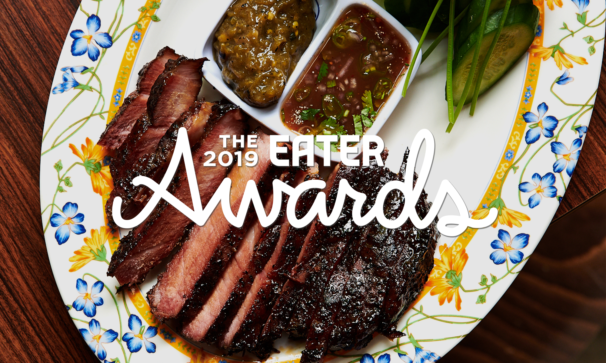 "A picture of a hunk of sliced meat with a brisket-like bark on the outside, served with two dips and leaves. Over the image is writing that reads, ""The Eater Awards"""