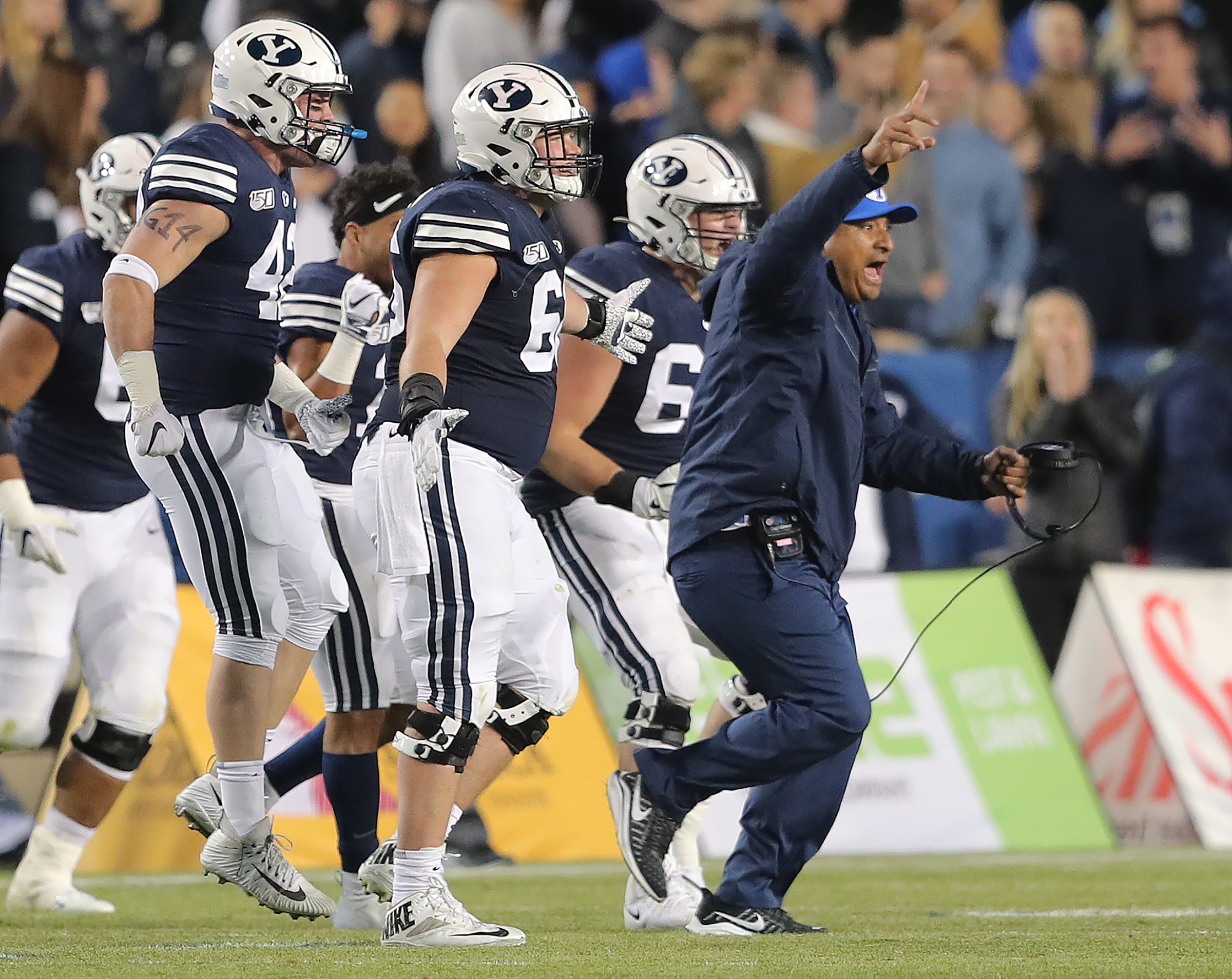 Brigham Young Cougars head coach Kalani Sitake leads his players out onto the field as BYU defeats Liberty in an NCAA football game in Provo, Utah on Saturday, Nov. 9, 2019. BYU won 31-24.