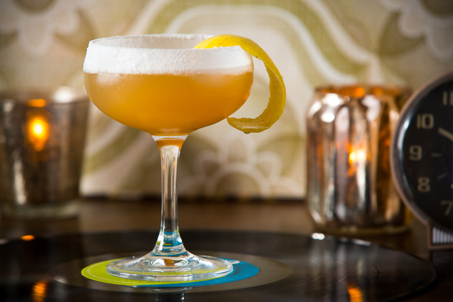 A frothy orange cocktail in a coupe glass.