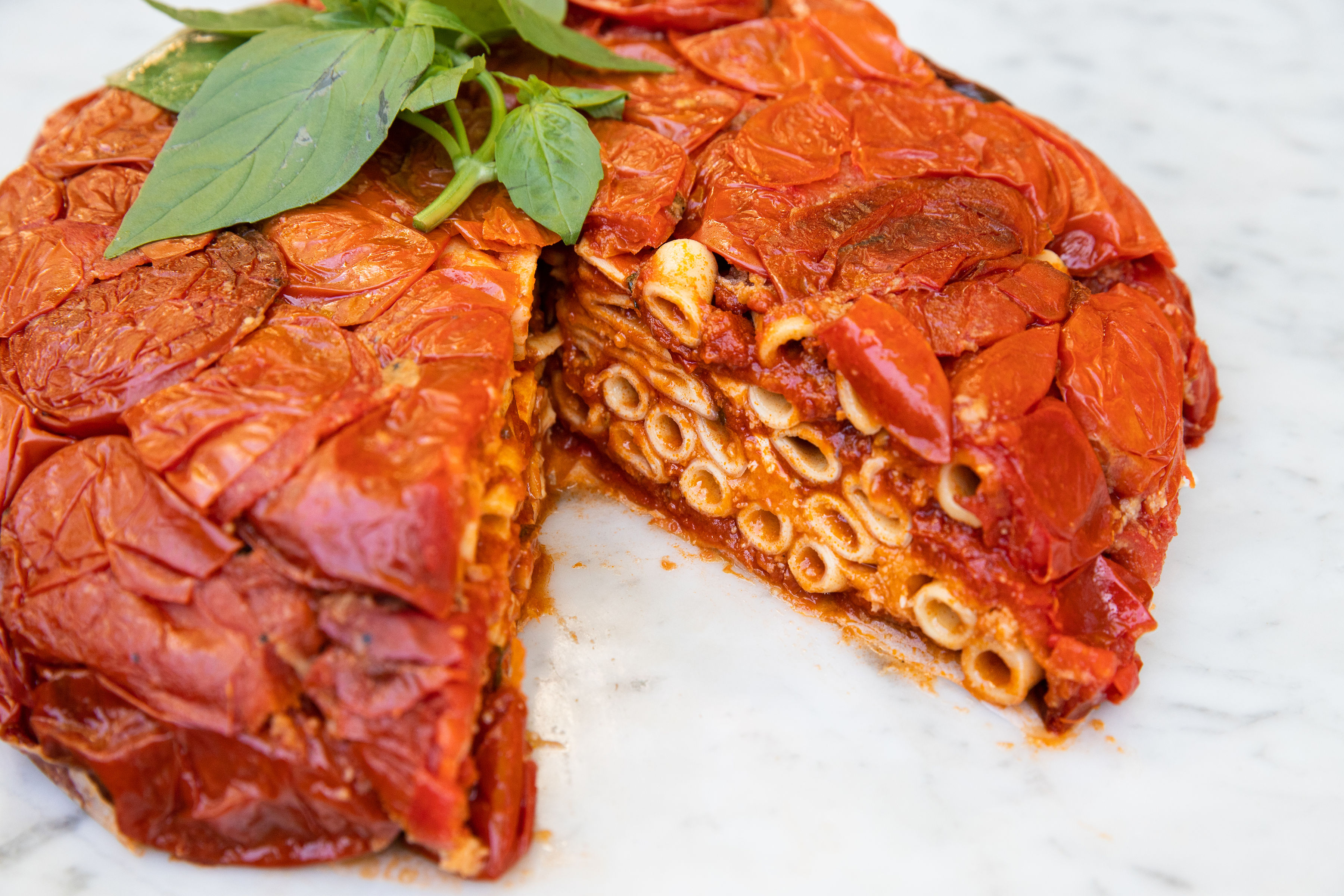 A big round cake of baked ziti in tomato sauce with a slice cut out