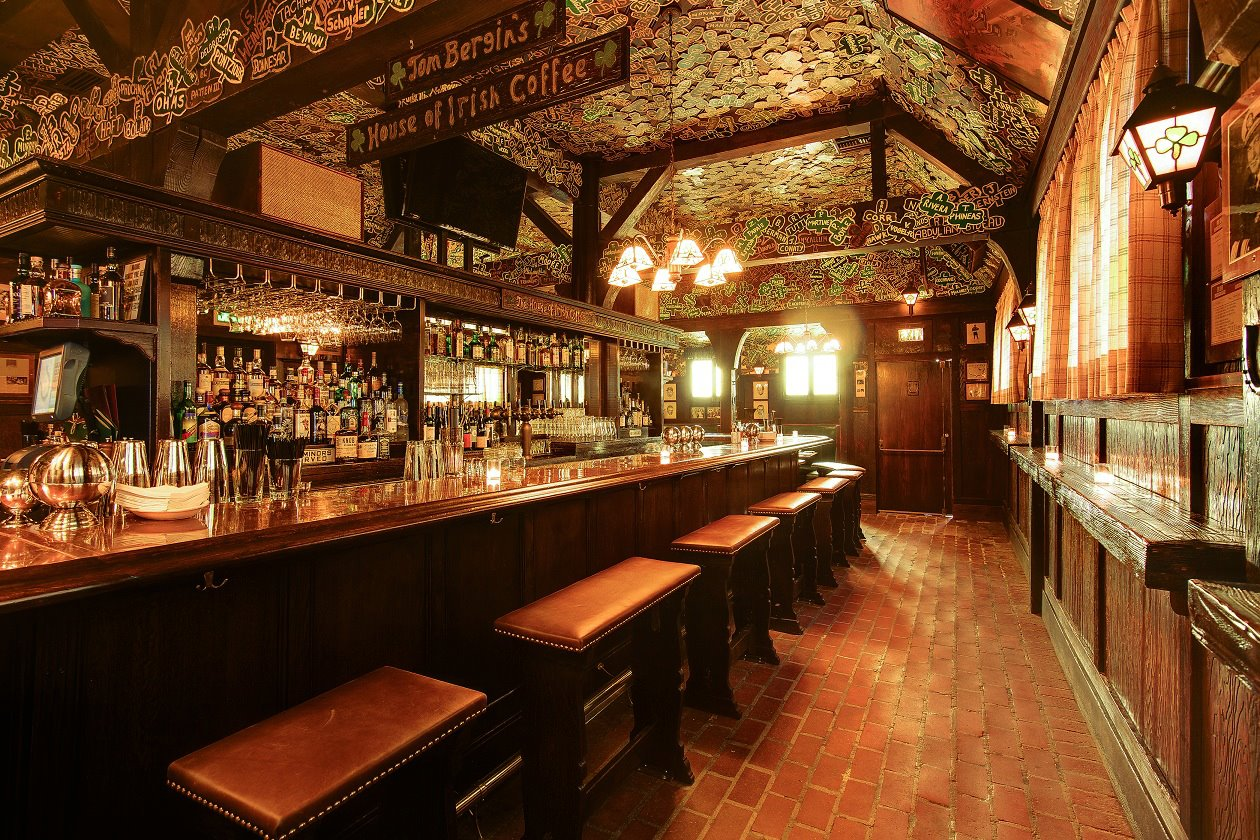 The warm glow of an Irish pub with lots of wood and shamrocks on the ceiling.