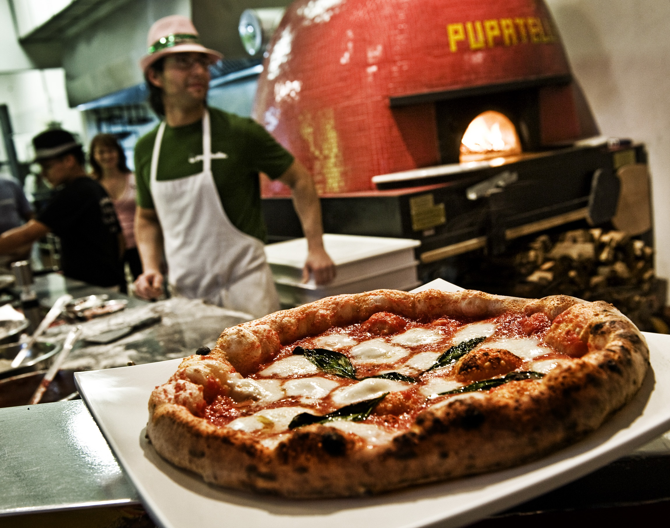A Margherita pizza from Pupatella is displayed on a white plate in front of the wood-burning oven