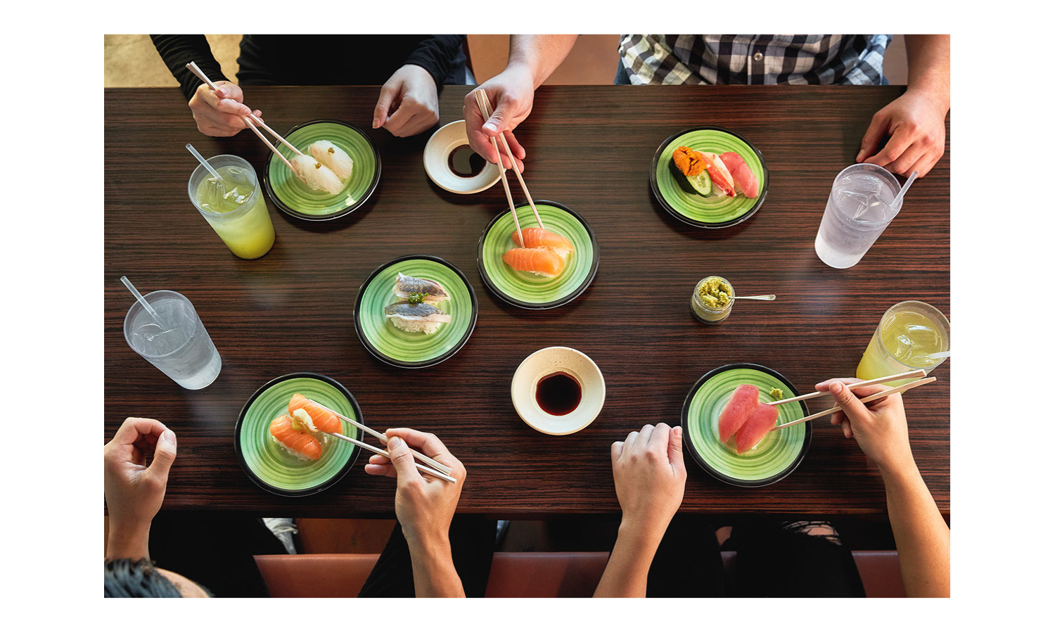Hands holding chopsticks reach across a conveyor belt to pluck pieces of sushi from plates moving slowly past