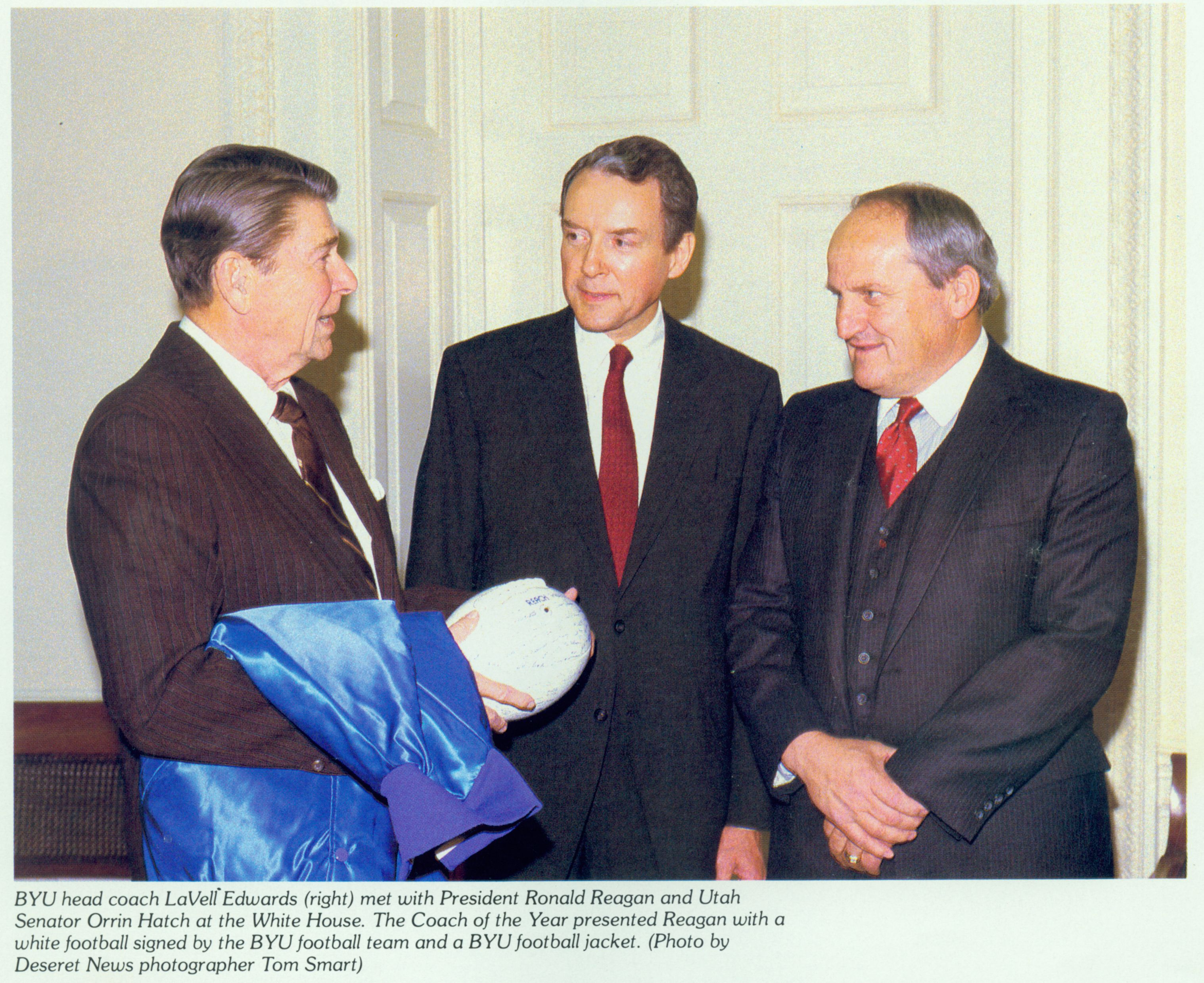 BYU head coach LaVell Edwards, right, meets with President Ronald Reagan and Sen. Orrin Hatch, R-Utah, at the White House. The Coach of the Year presented Reagan with a white football signed by the BYU football team and a BYU football jacket.