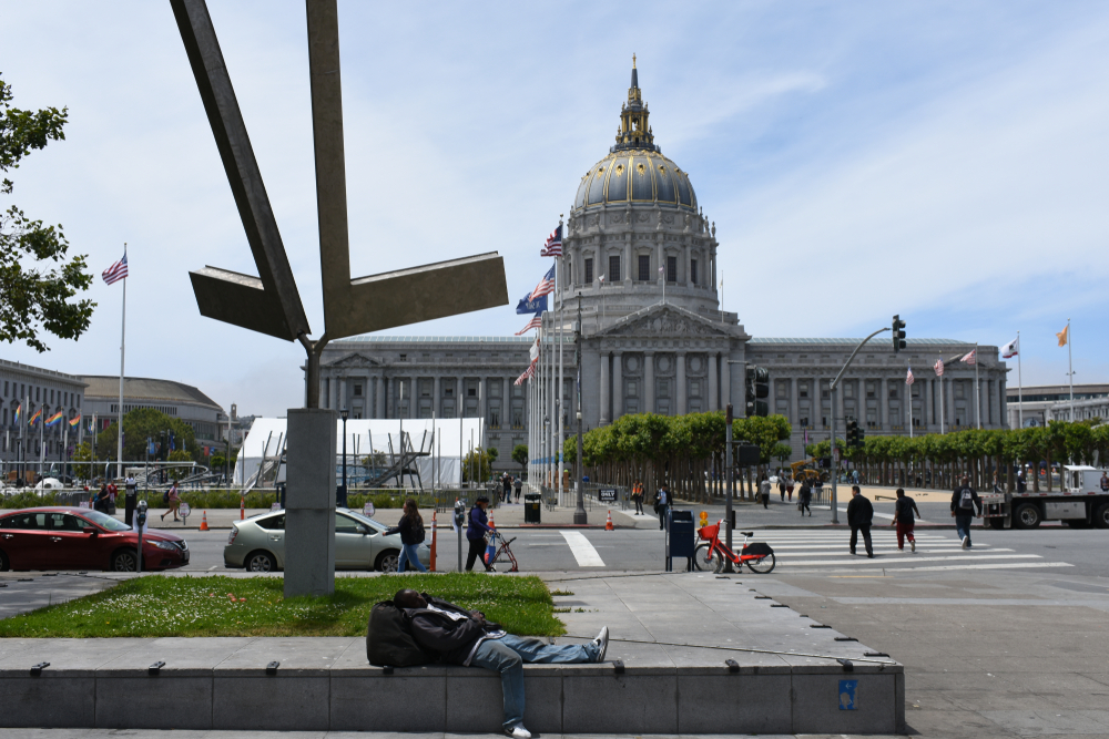 A man sleeping underneath a windmill-like piece of public art, with a white domed building (SF City Hall) in the background.