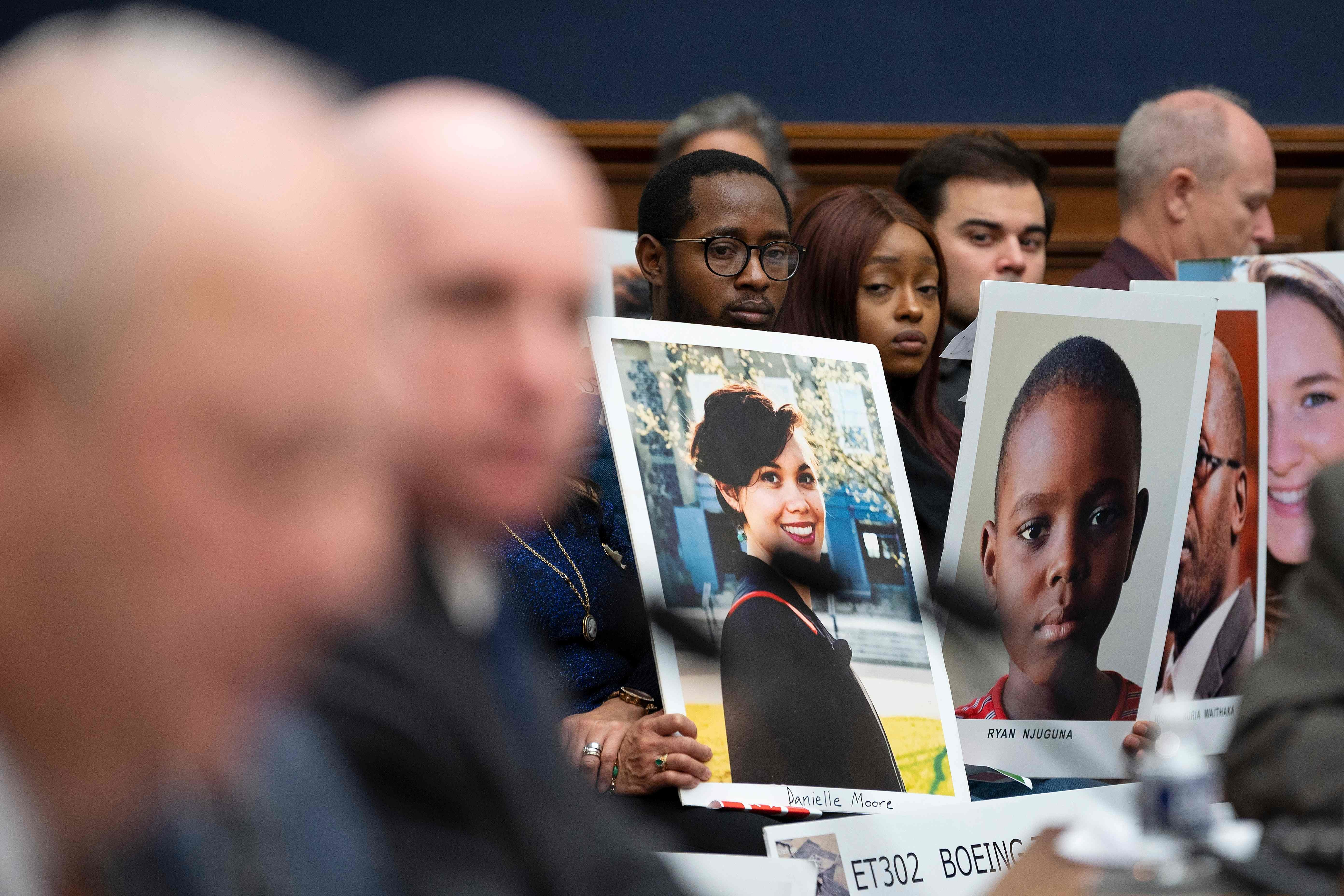 People hold up pictures of the victims of Boeing 737 MAX accidents as FAA Administrator Stephen Dickson testifies Wednesday on Capitol Hill.