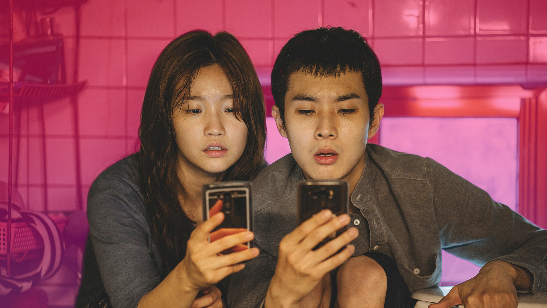 Ki-jung (Park So-dam) and Ki-woo (Choi Woo-shik) from the film 'Parasite' stare intently at their phones