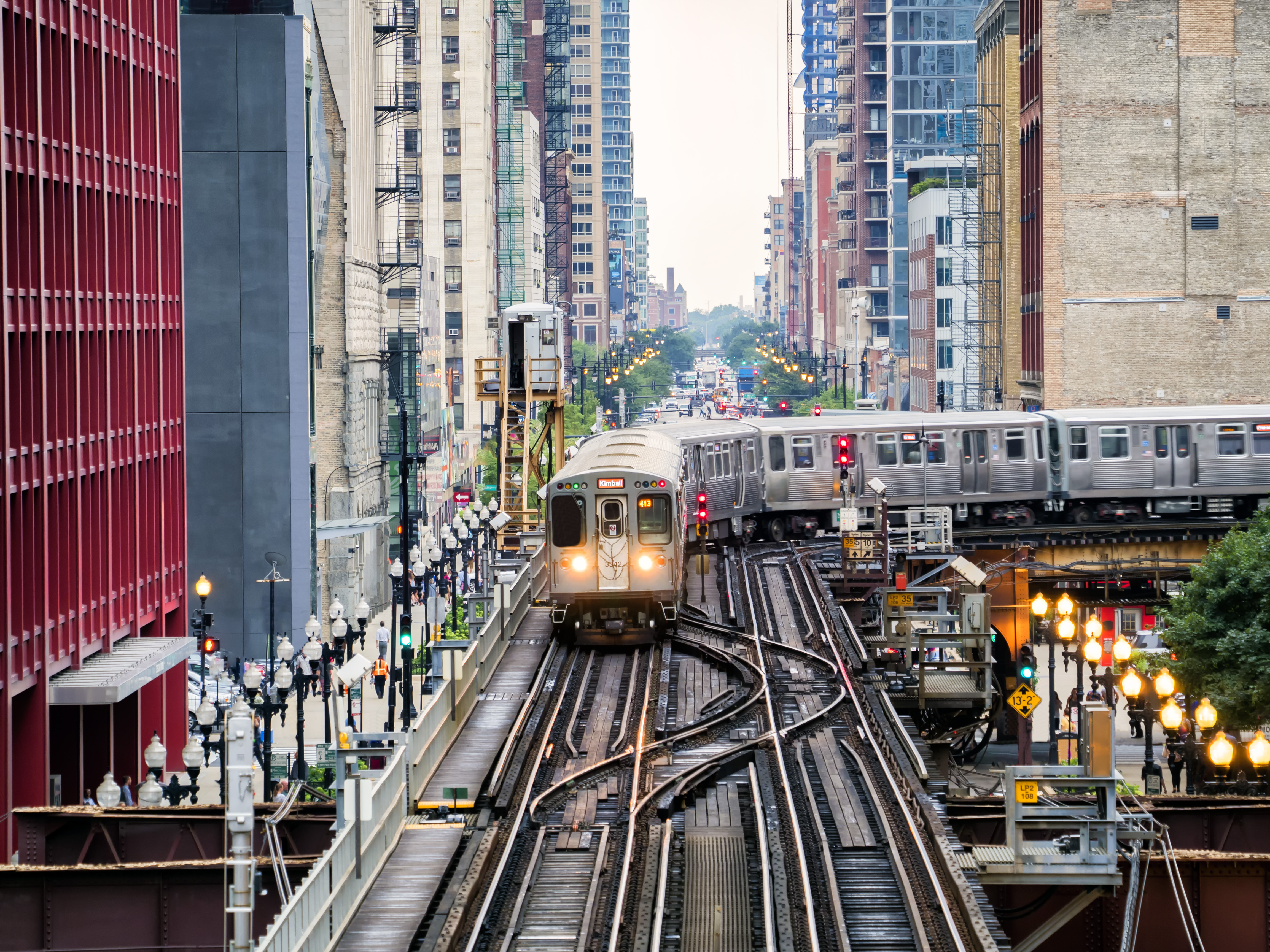 A view of the elevated train tracks and a CTA car running between buildings.